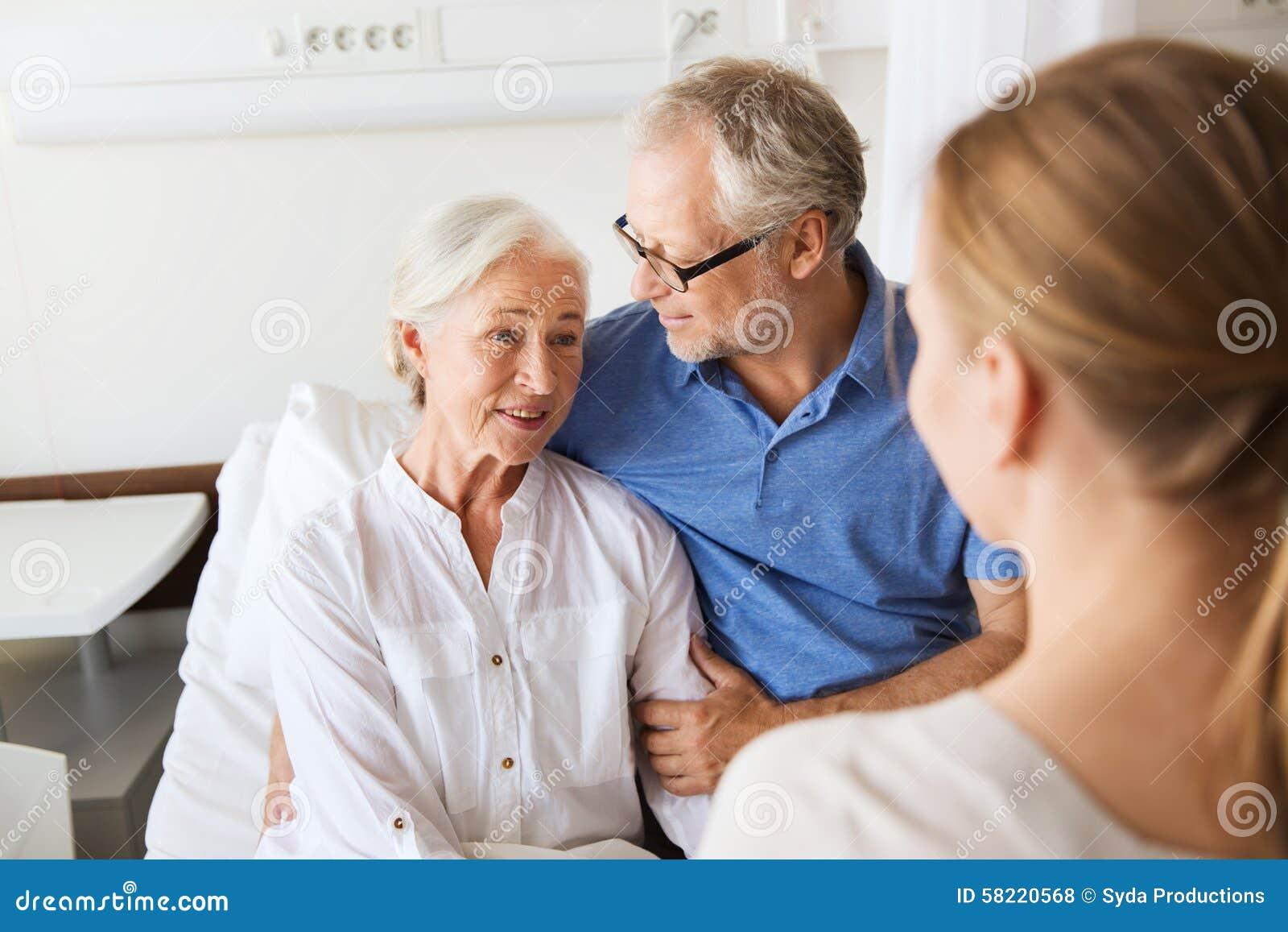 Famiglia felice che visita donna senior all ospedale
