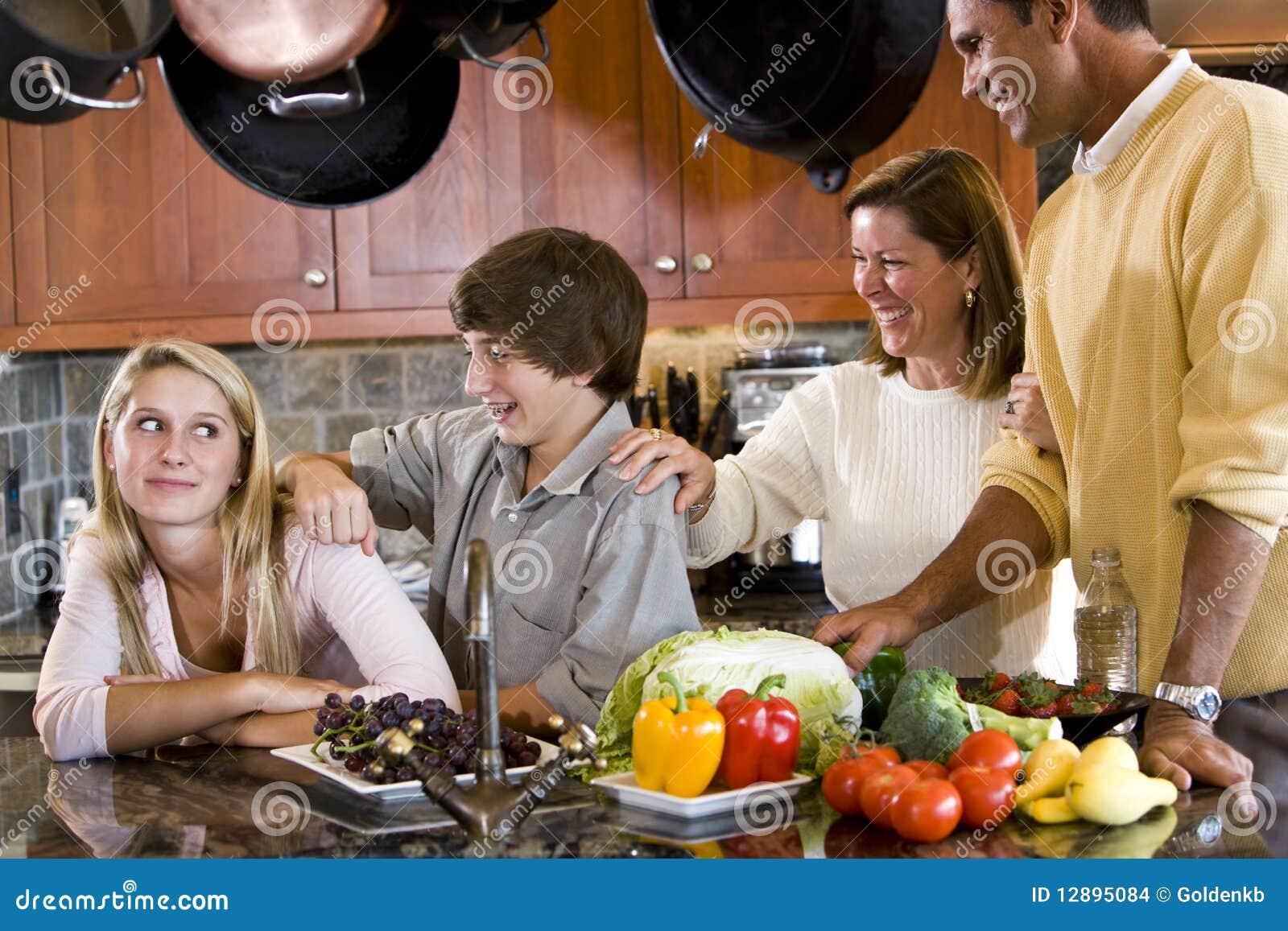 Famiglia felice con gli adolescenti che sorridono nella cucina