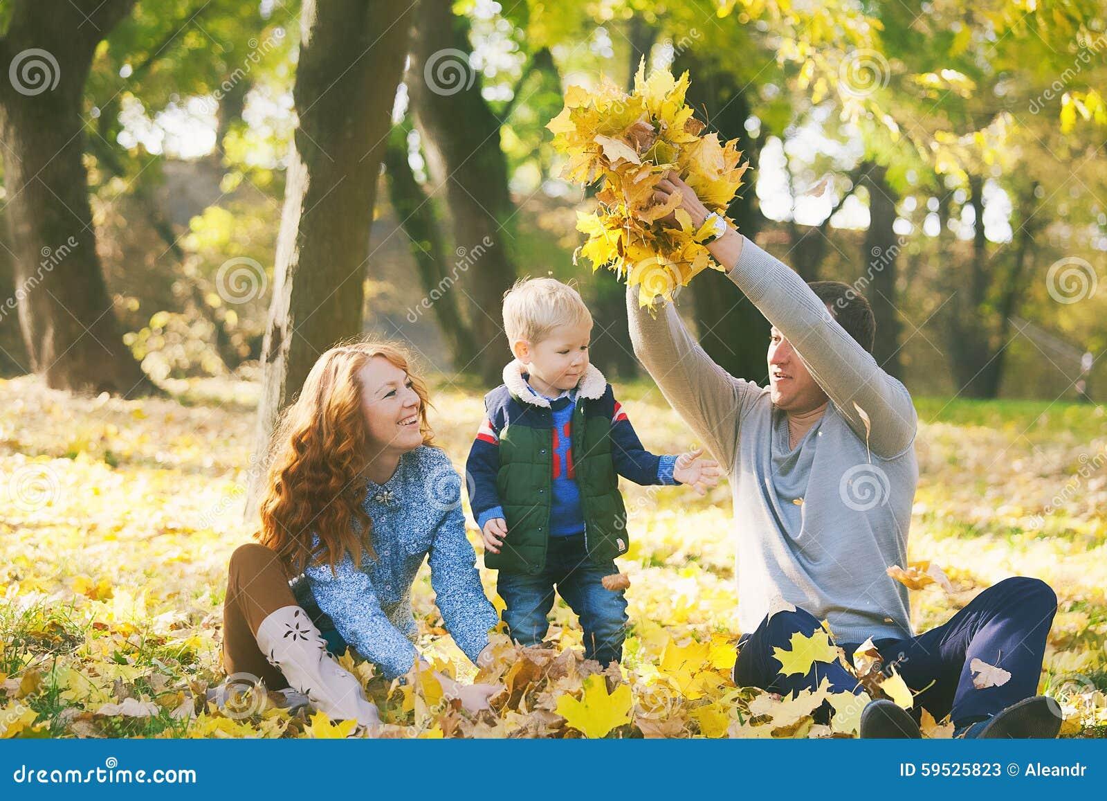 Famiglia felice divertendosi nel parco urbano di autunno