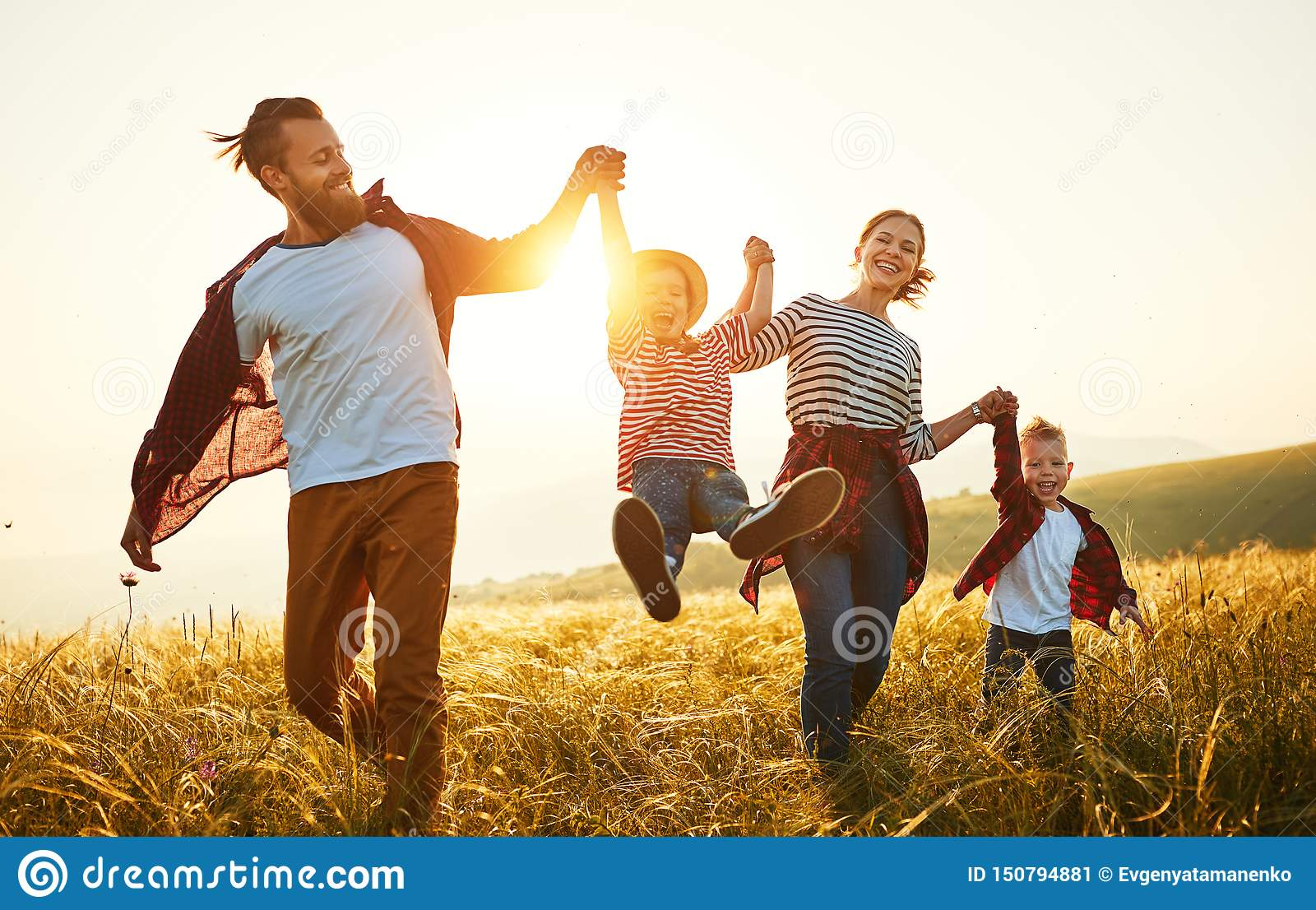 Famiglia felice: madre, padre, bambini figlio e figlia sul tramonto
