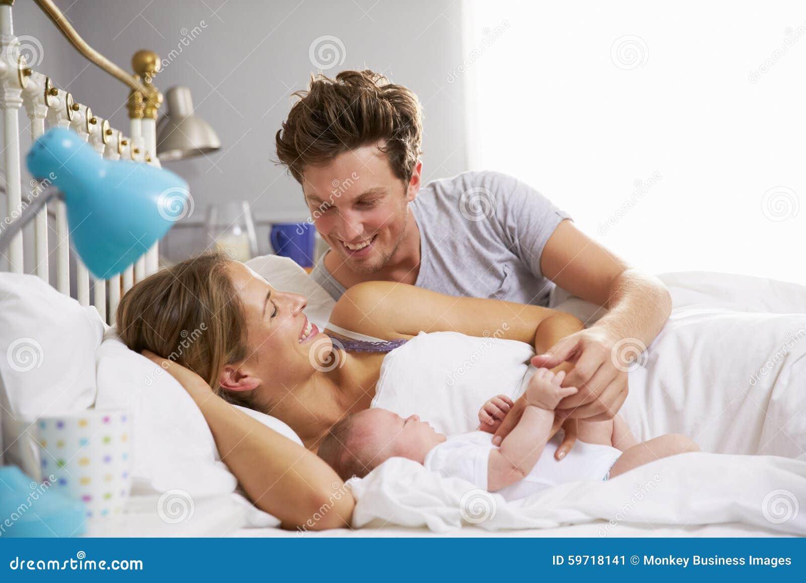 Famiglia a letto che tiene la figlia addormentata del neonato