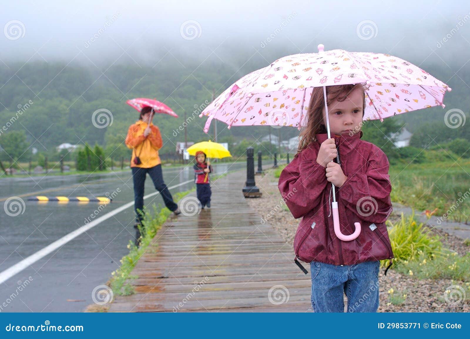 Famiglia sotto la pioggia immagine stock immagine di pink for Sotto la pioggia ombrelli
