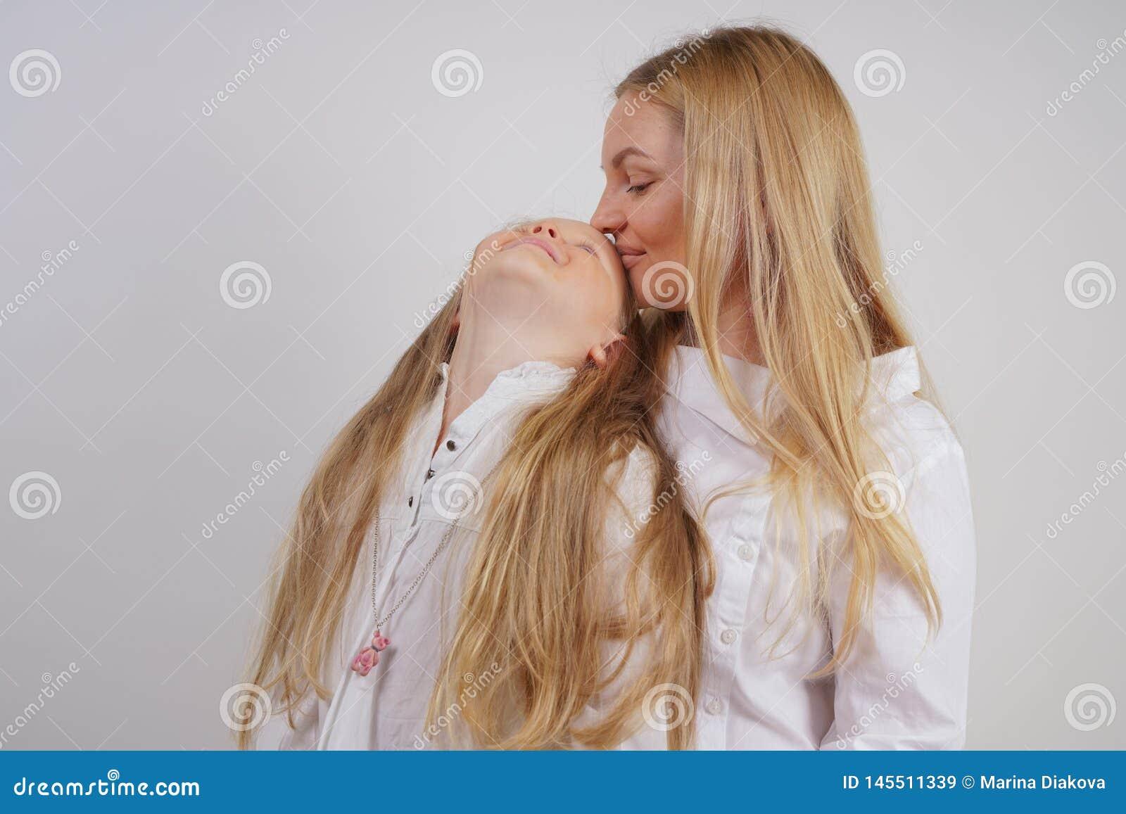 Famiglia reale della madre e della figlia caucasiche in camice bianche nei precedenti dello studio