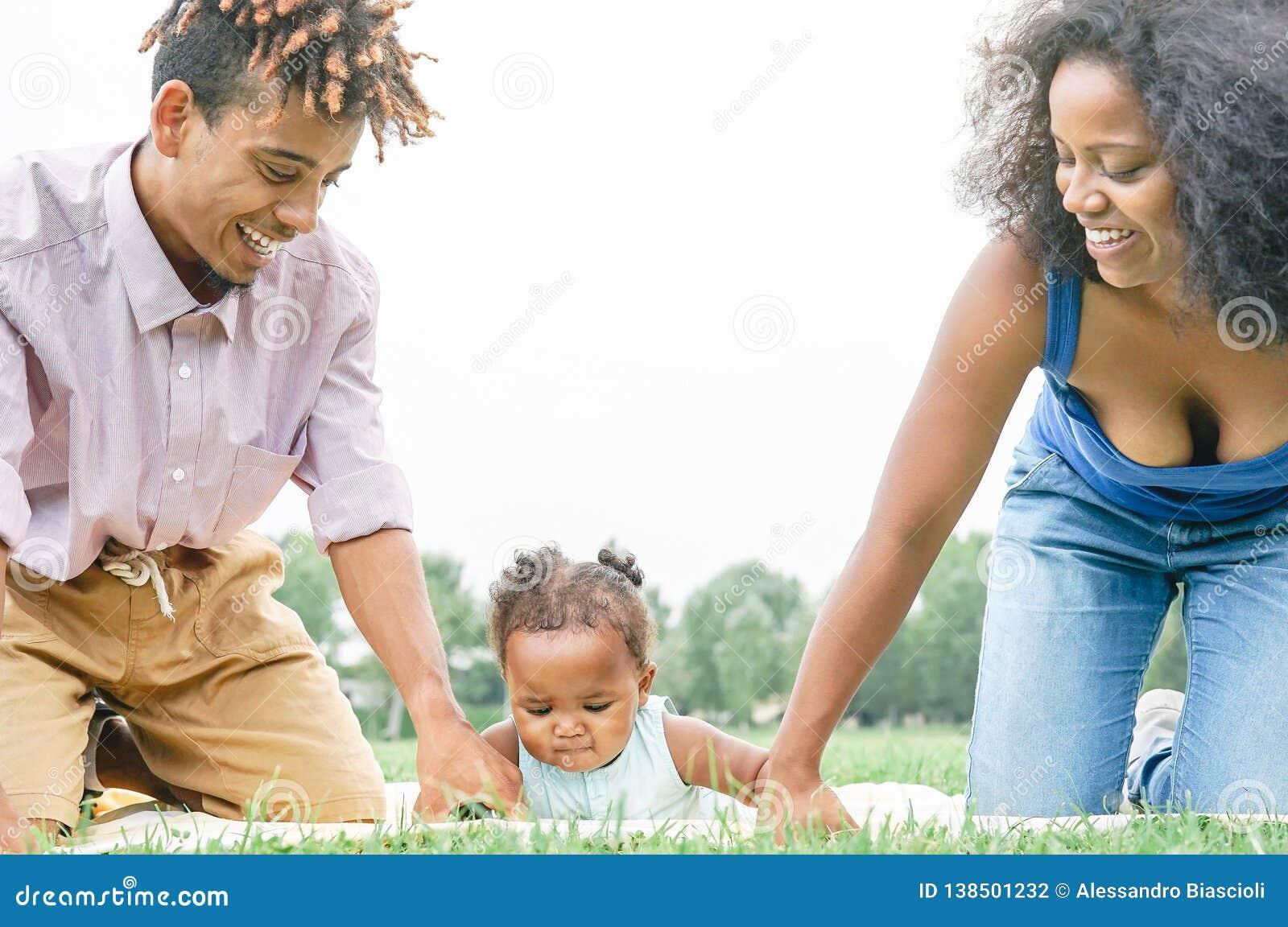 Familia africana feliz que se divierte que hace comida campestre en parque público - madre y padre que juegan con su hija al aire