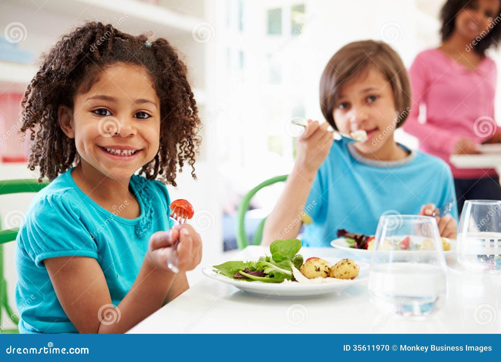 Familia afroamericana que come la comida en casa junto