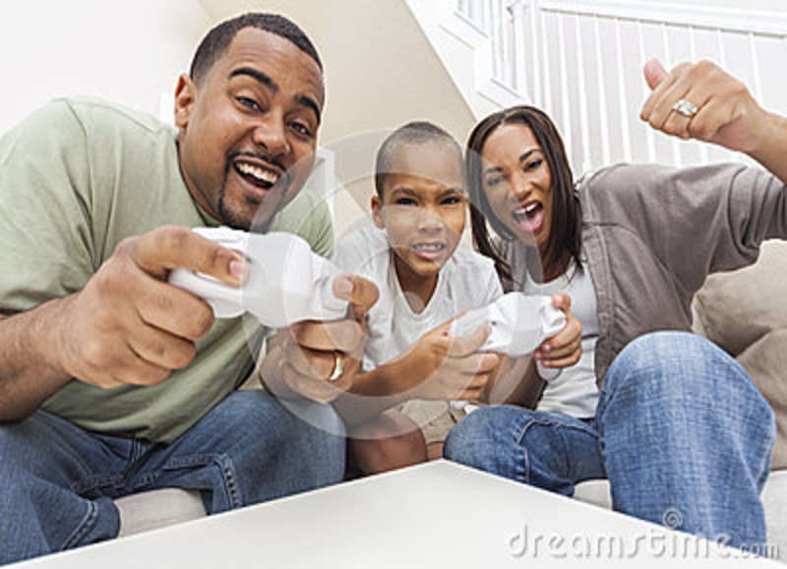 Familia afroamericana que se divierte que juega al juego de la consola informática