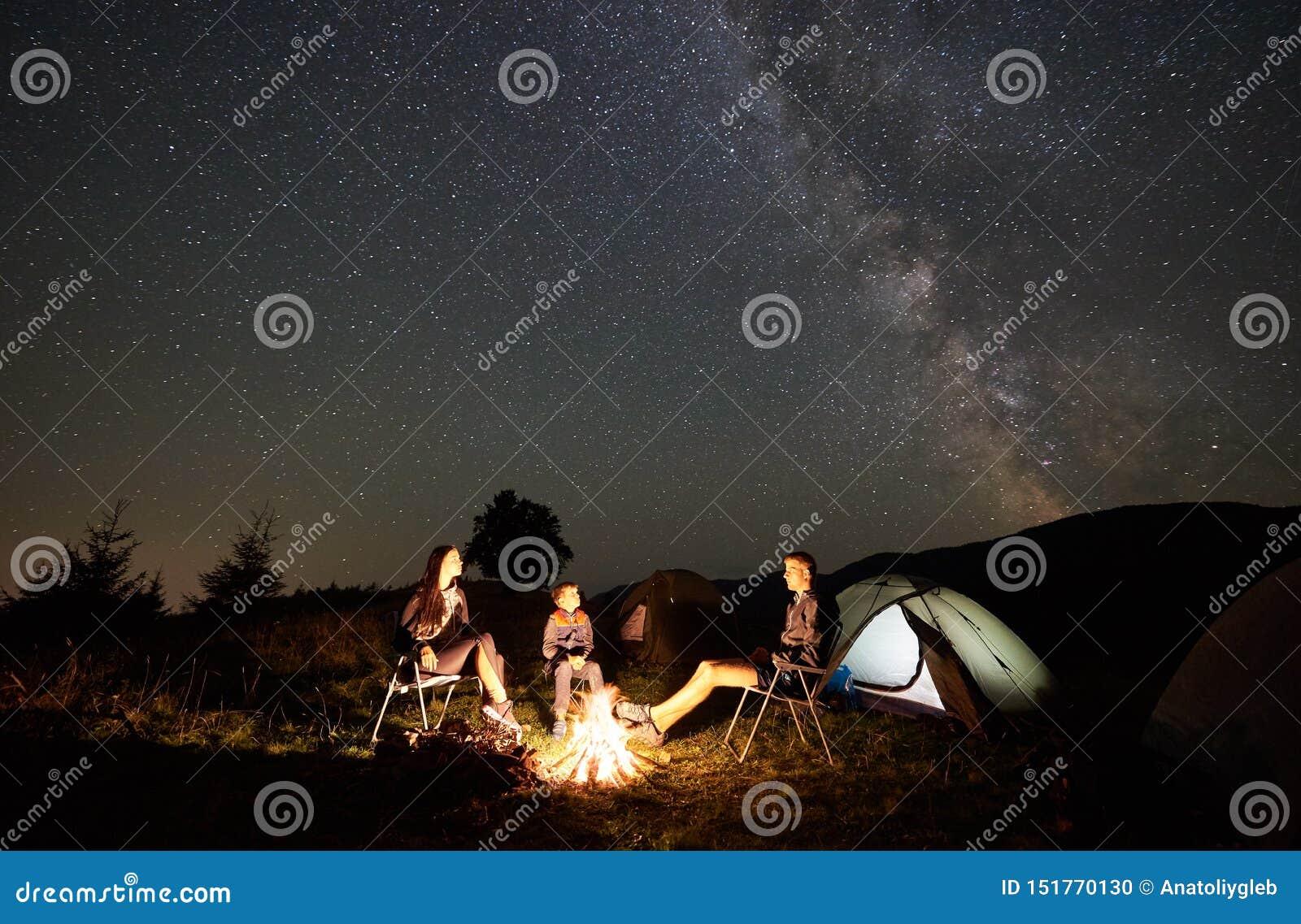 Familia al lado del campo, hoguera, tienda debajo del cielo estrellado de la noche