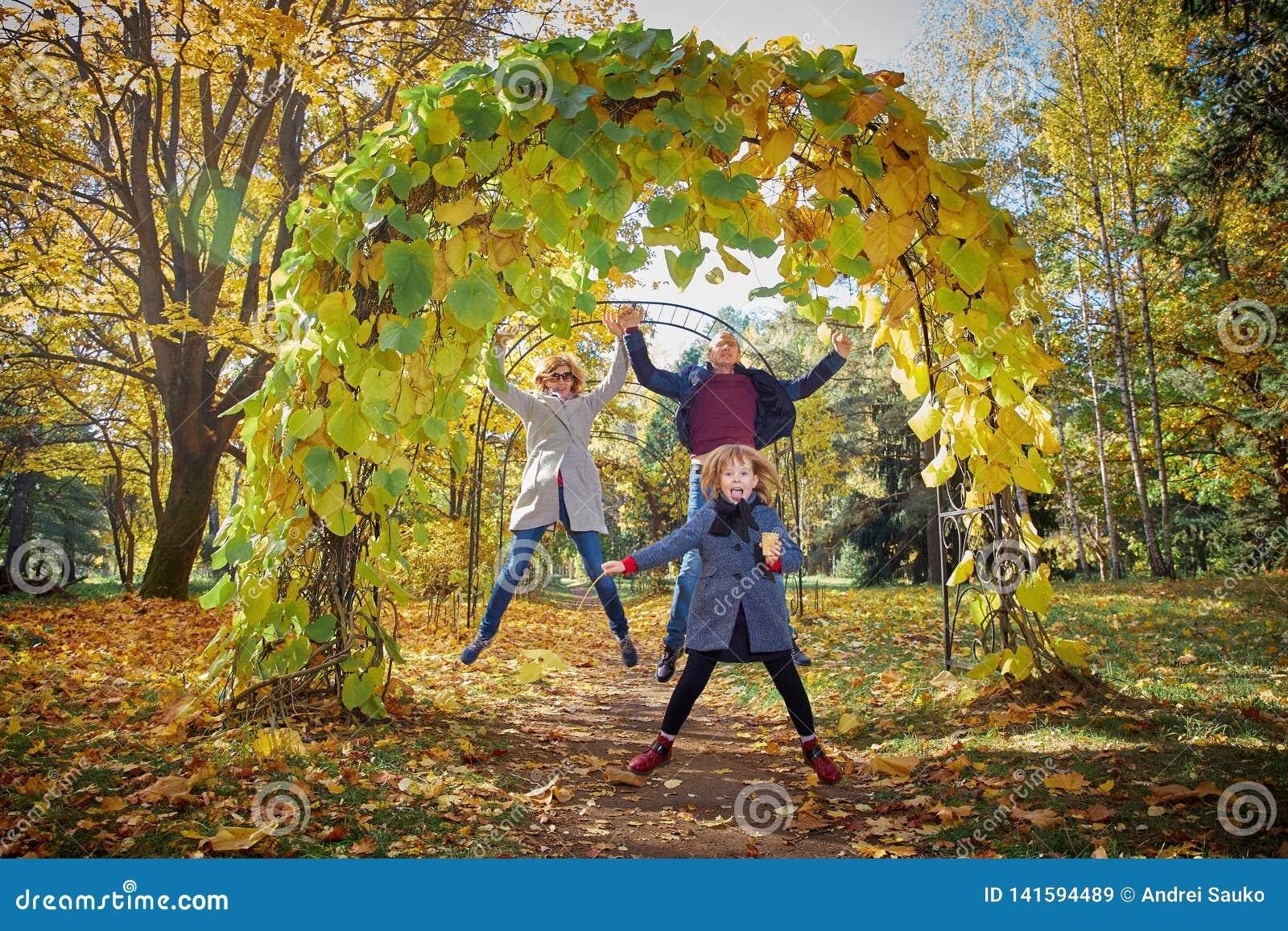 Familia alegre en el parque del otoño