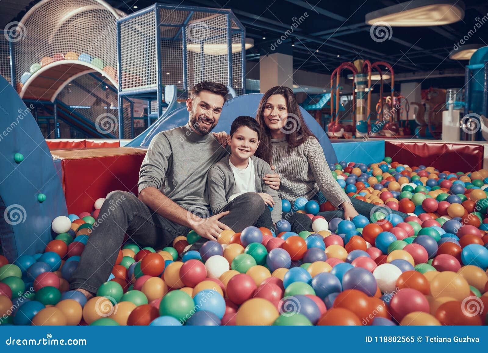 Familia alegre que se sienta en piscina con las bolas