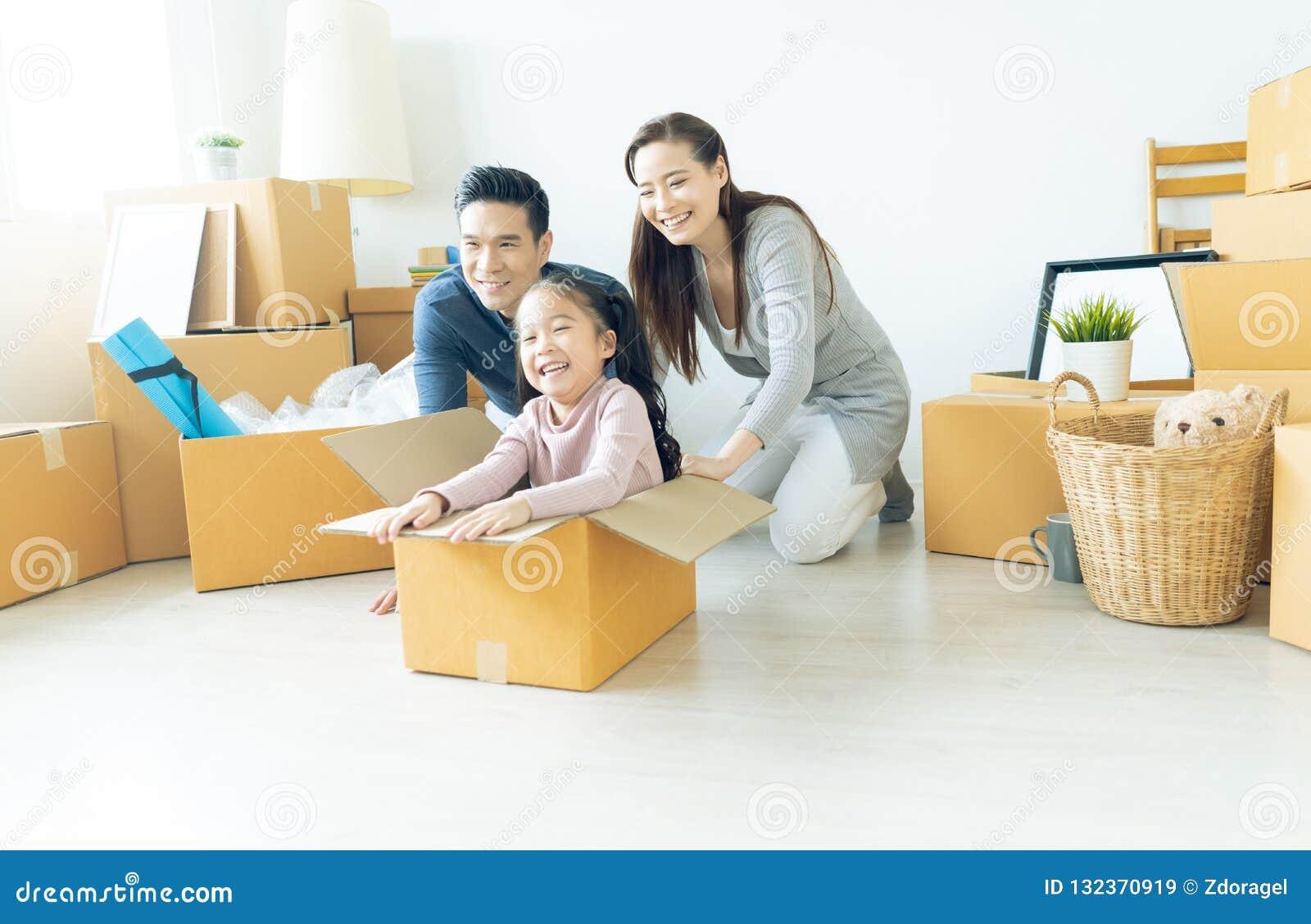 Familia asiática joven feliz de tres que se divierten que se mueve con cardboa