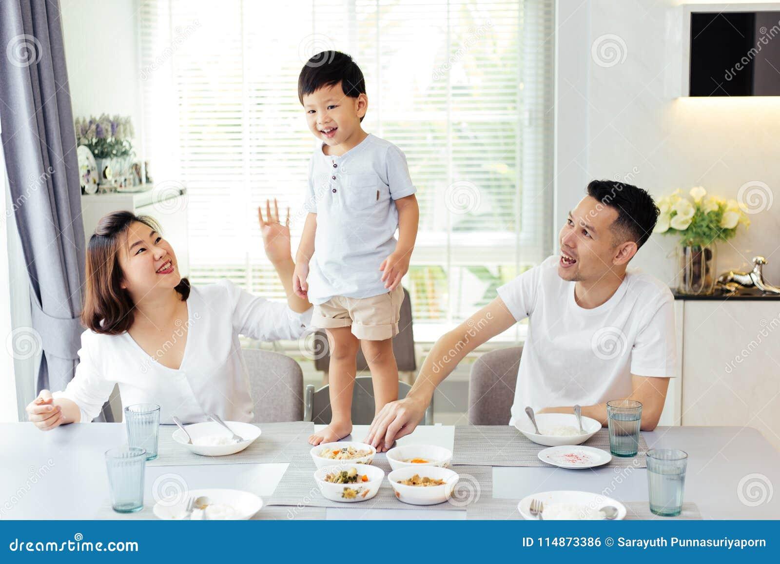 Familia asiática que mira a su niño pues él es resuelto y orgulloso finalmente colocarse en la mesa de comedor