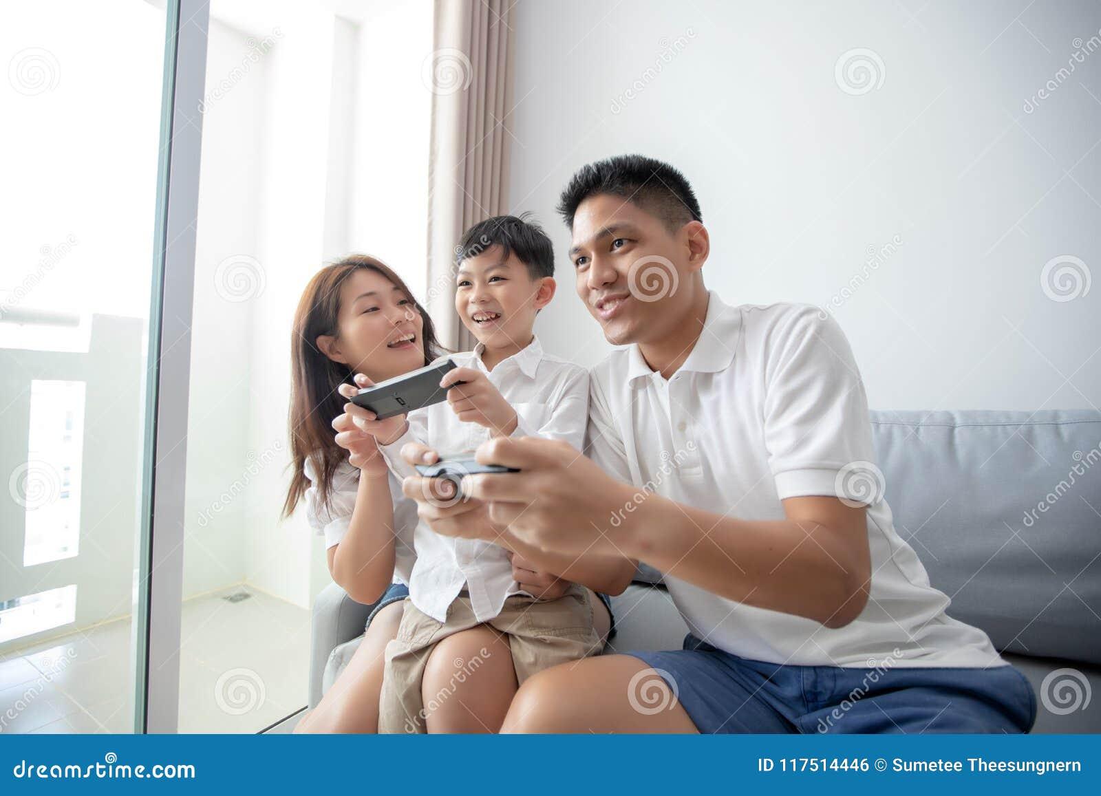 Familia asiática que se divierte que juega a juegos de la consola informática juntos,