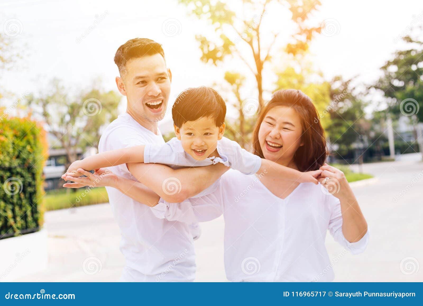 Familia asiática que se divierte y que lleva a un niño en parque público