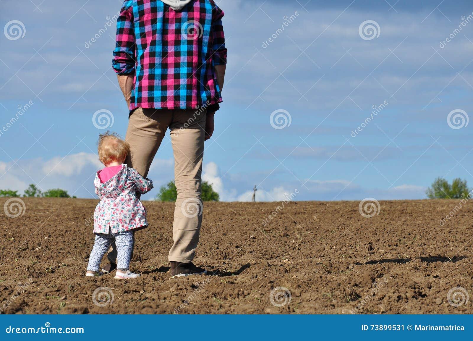 Familia cariñosa feliz Engendre y su muchacha del niño de la hija que juega y que abraza al aire libre en el campo La niña linda