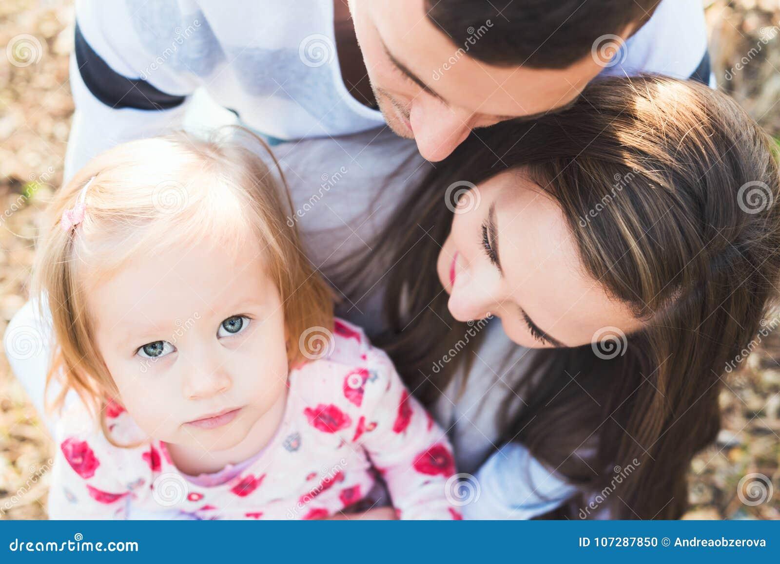 Familia cariñosa joven de tres, retrato sincero auténtico de la familia del aire libre
