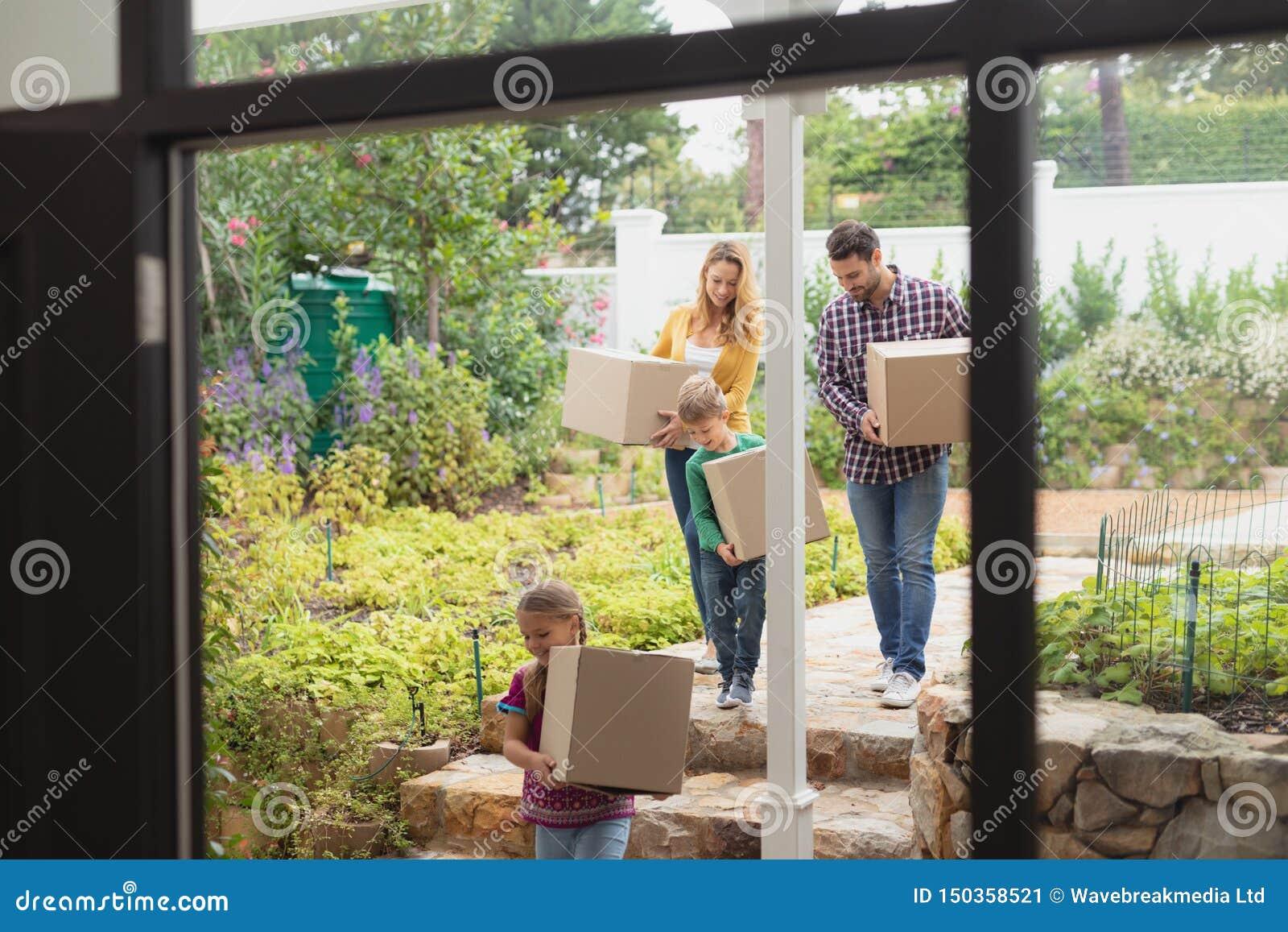 Familia caucásica feliz con las cajas de cartón que camina hacia hogar