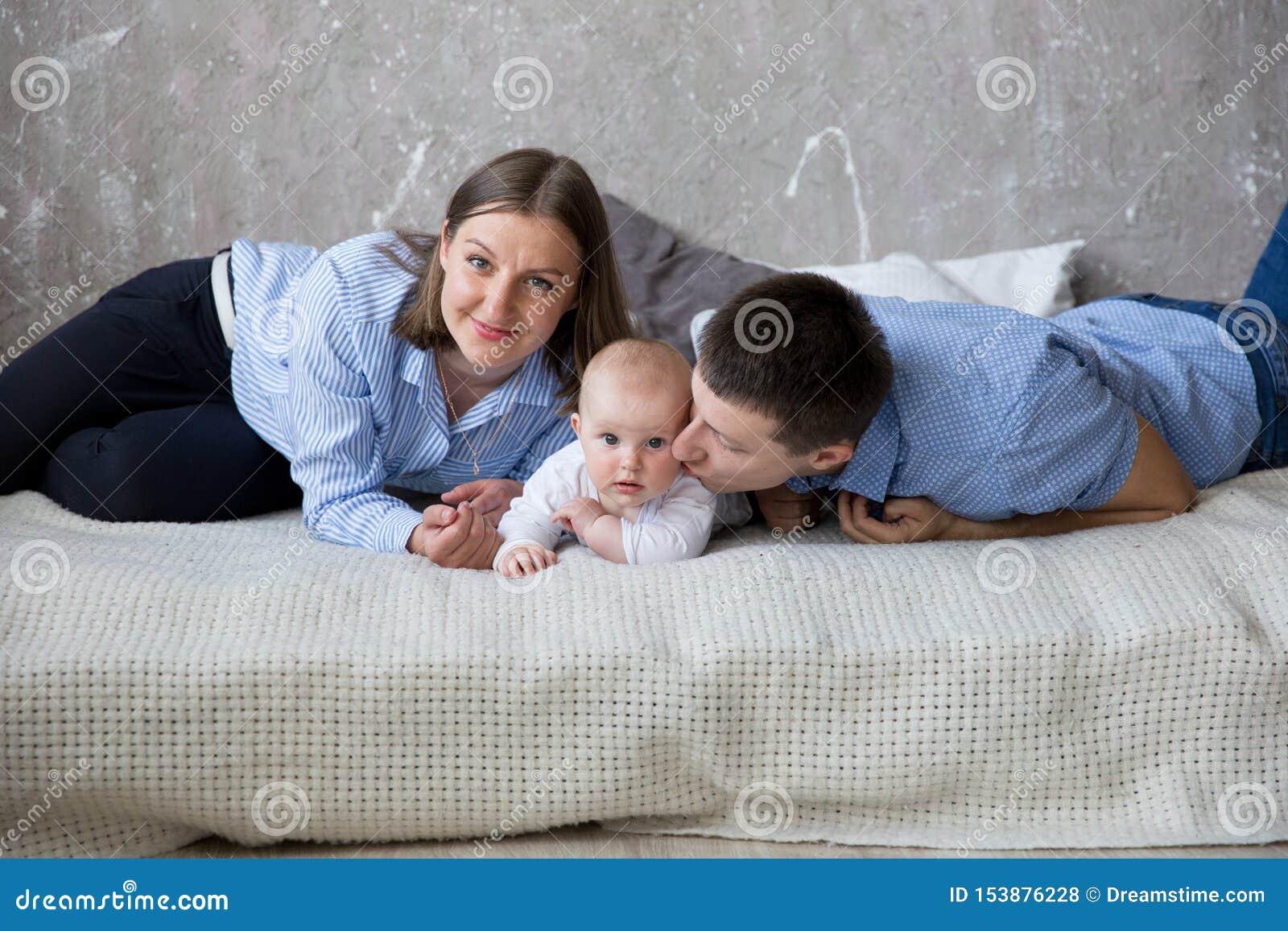 Familia caucásica joven feliz que miente en cama