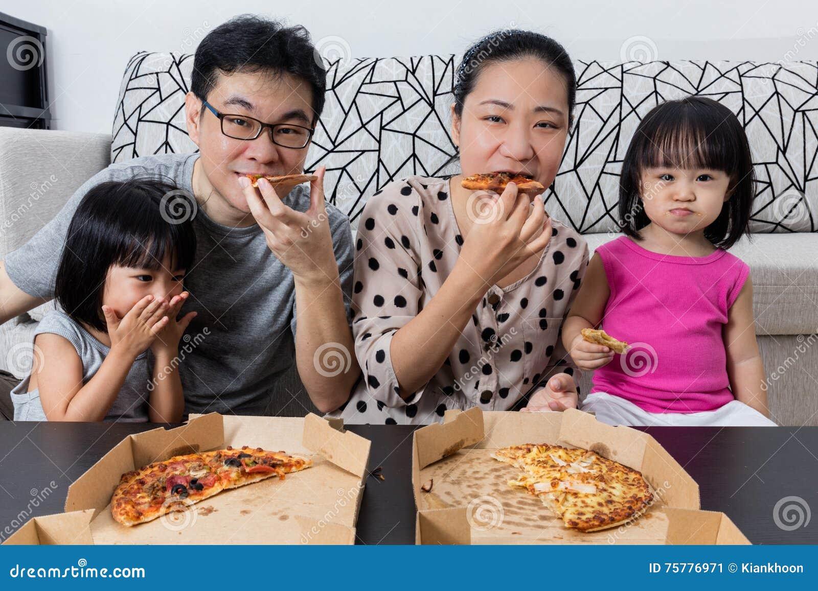 Familia china asiática feliz que come la pizza junta