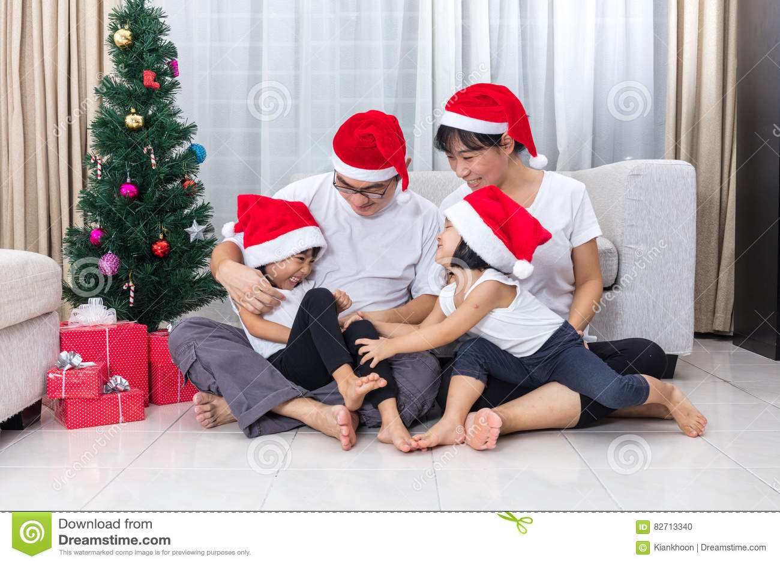 Familia china asiática feliz que se sienta en el piso que celebra Chri