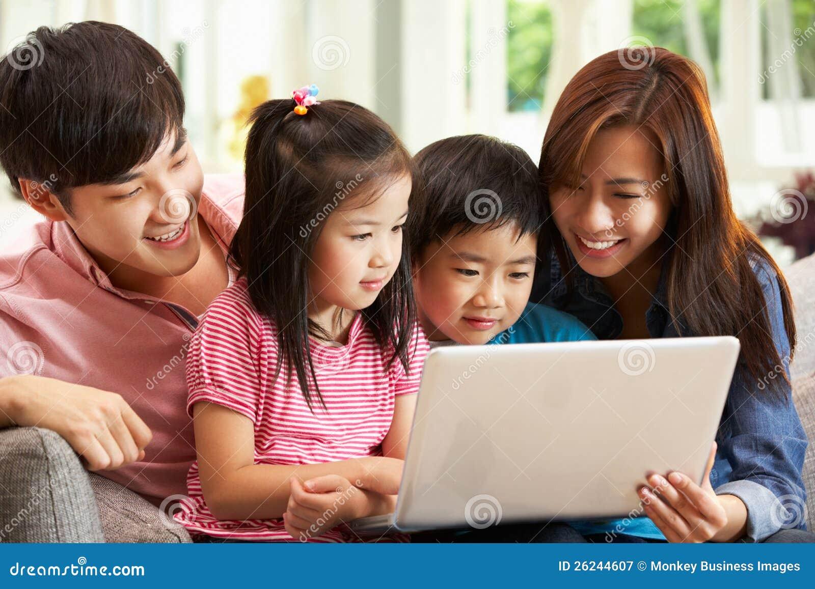 Familia china usando la computadora portátil mientras que se relaja