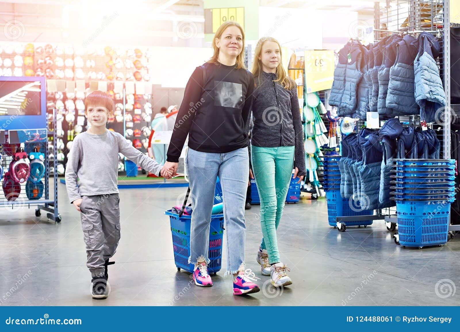 Familia con el carro de la compra en tienda de las mercancías del deporte