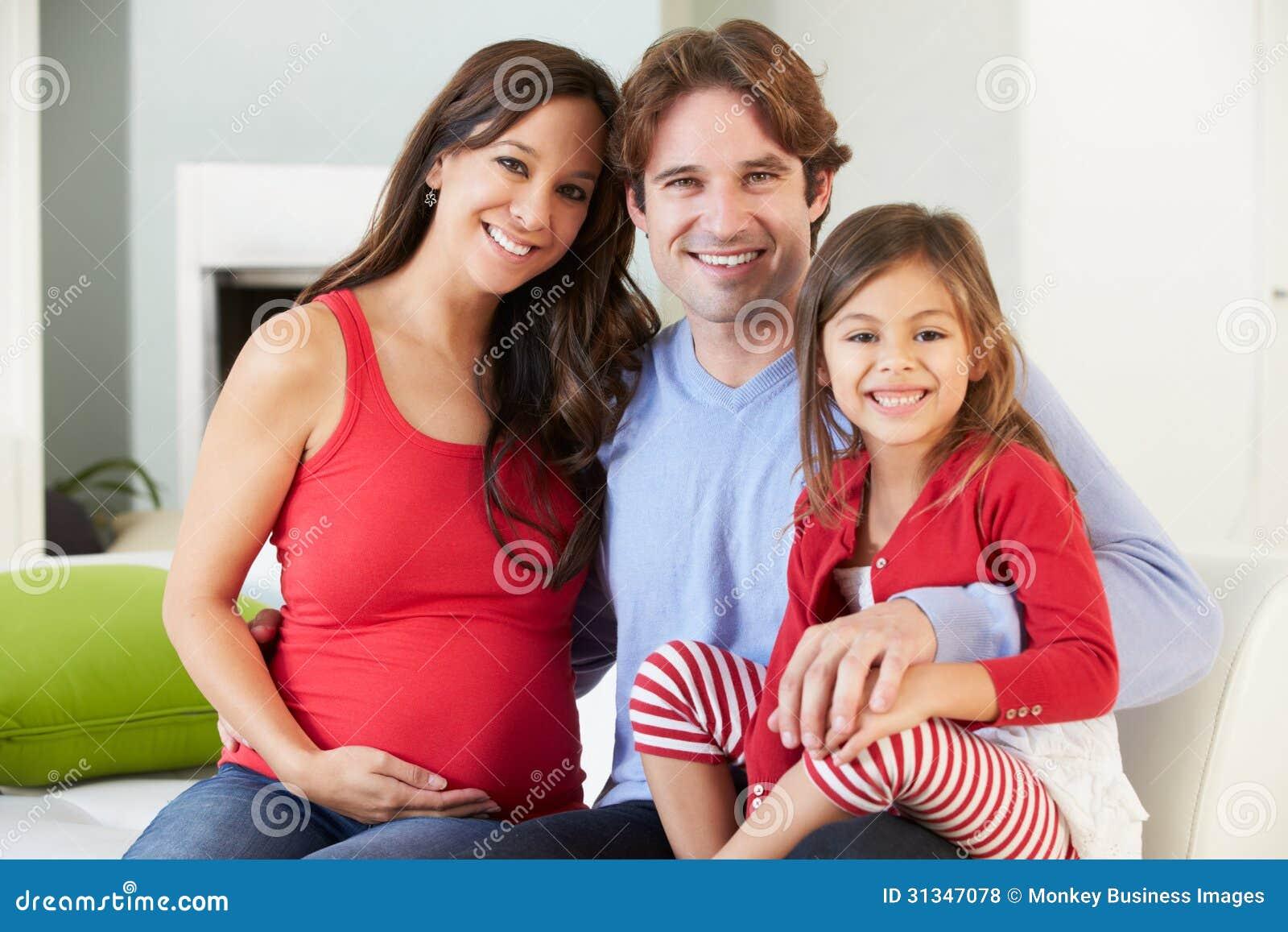 Familia con la madre embarazada que se relaja en Sofa Together