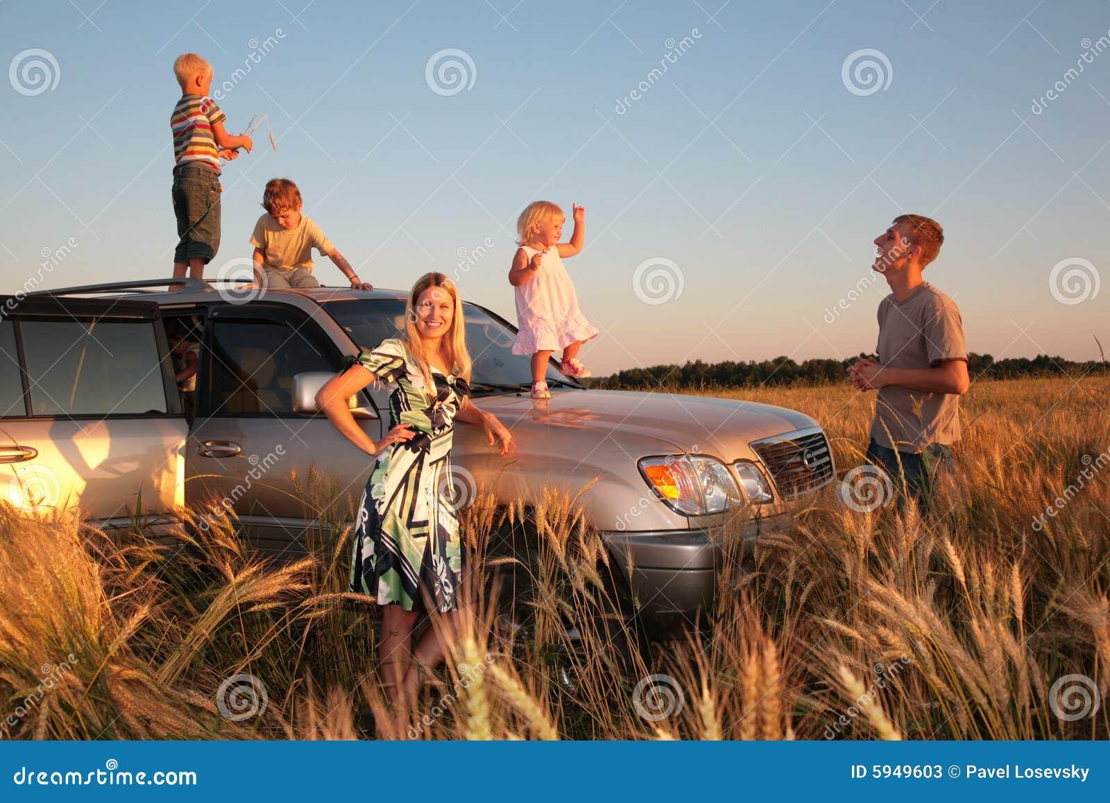 Familia con los niños en el coche campo a través