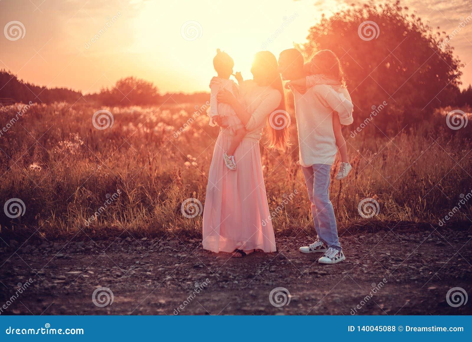 Familia con los niños en la puesta del sol