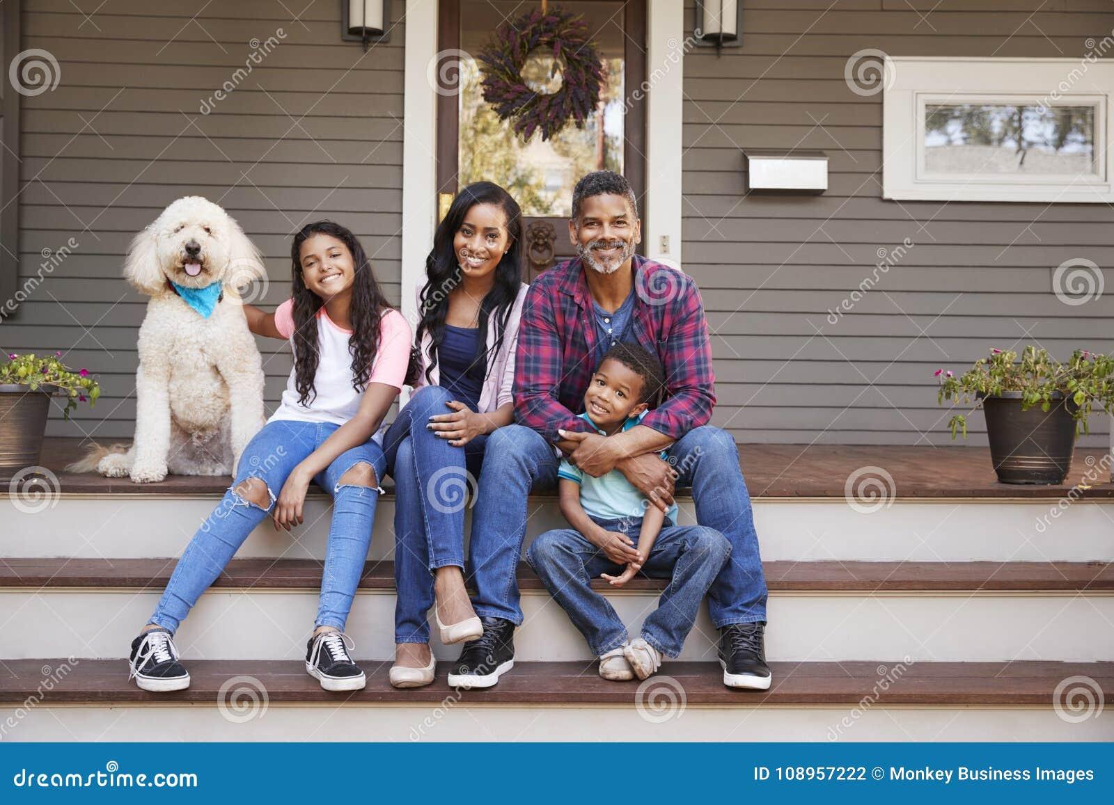 Familia con los niños y el perro casero Sit On Steps Of Home
