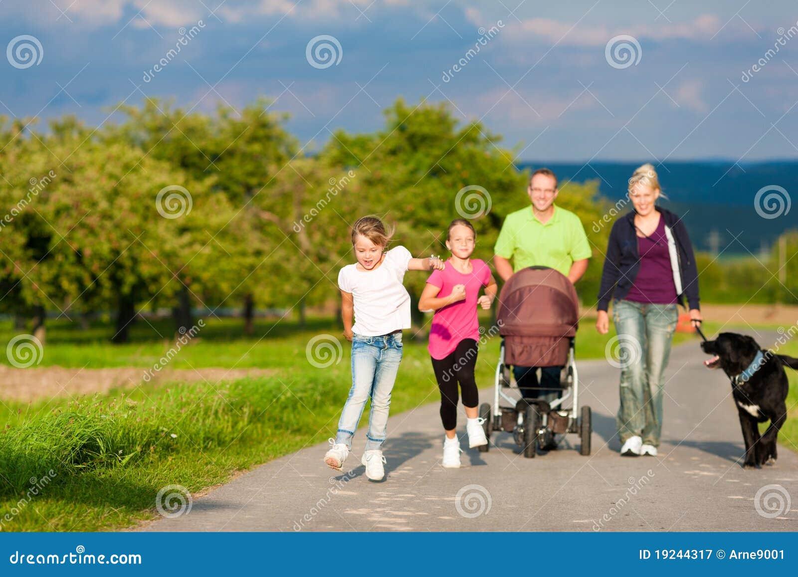Familia con los niños y el perro que tienen caminata