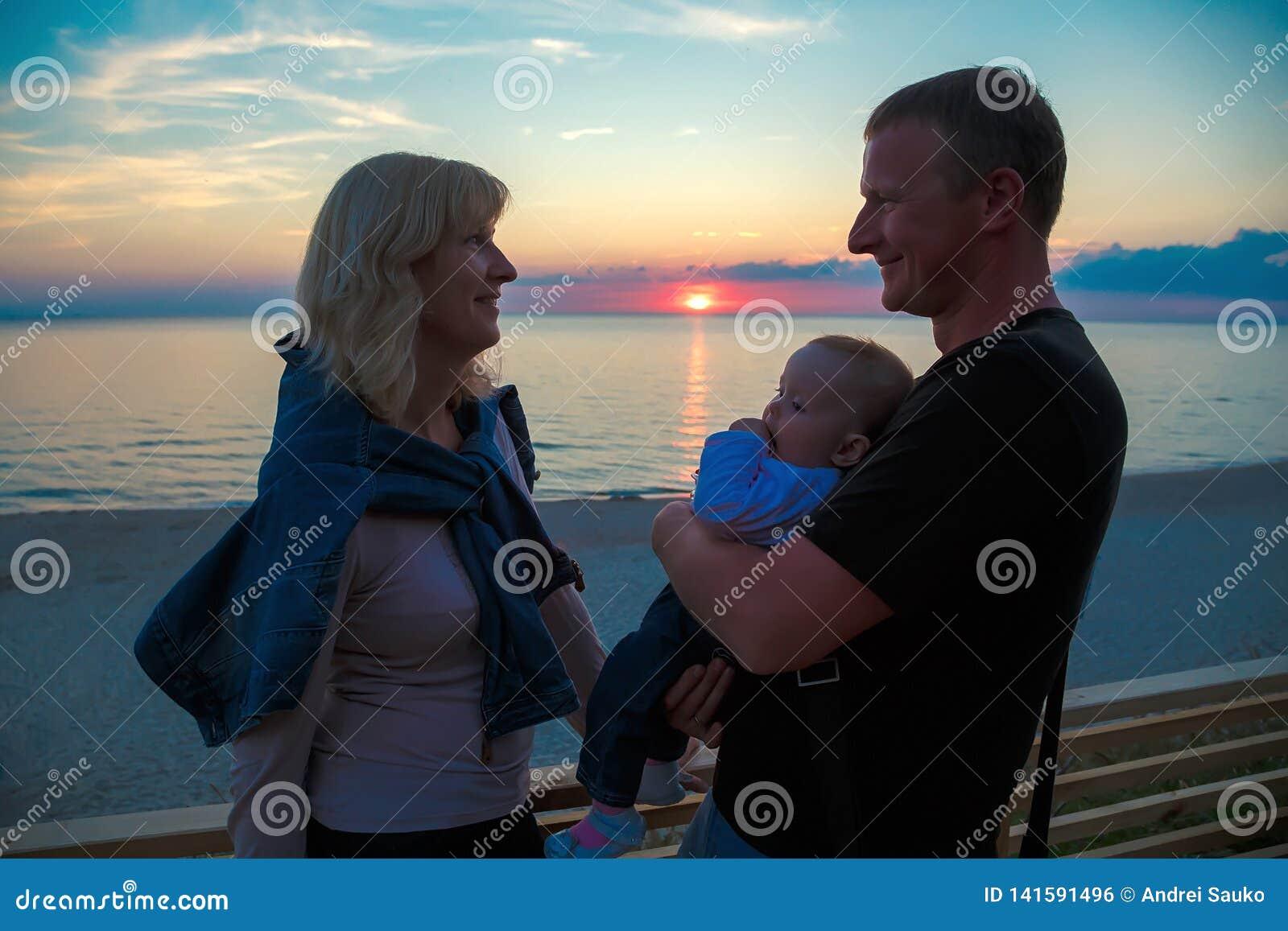Familia con un niño joven en la orilla del mar Báltico