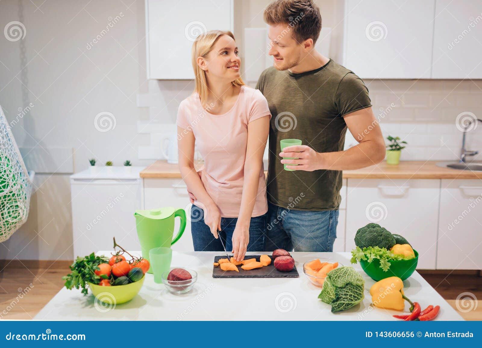 Familia de amor del vegano que cocina verduras crudas en la cocina Verdura del corte de la mujer joven mientras que su marido beb