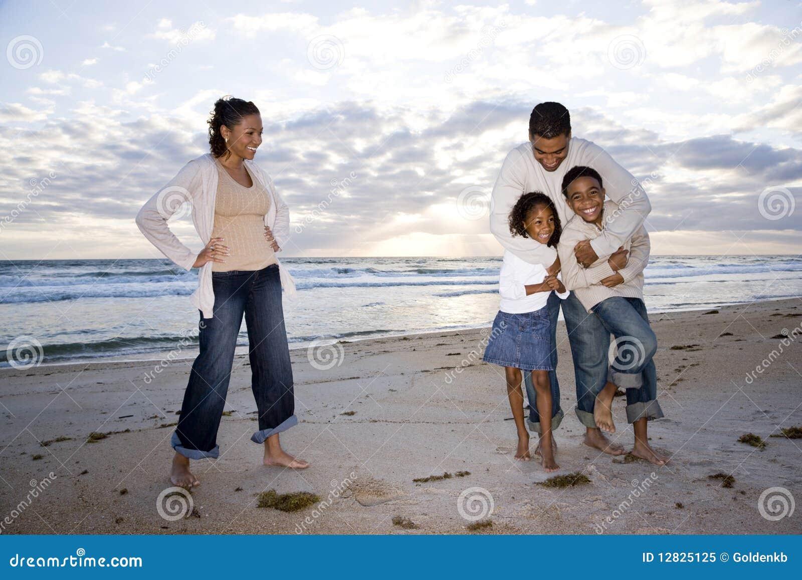 Familia de cuatro miembros feliz del African-American en la playa