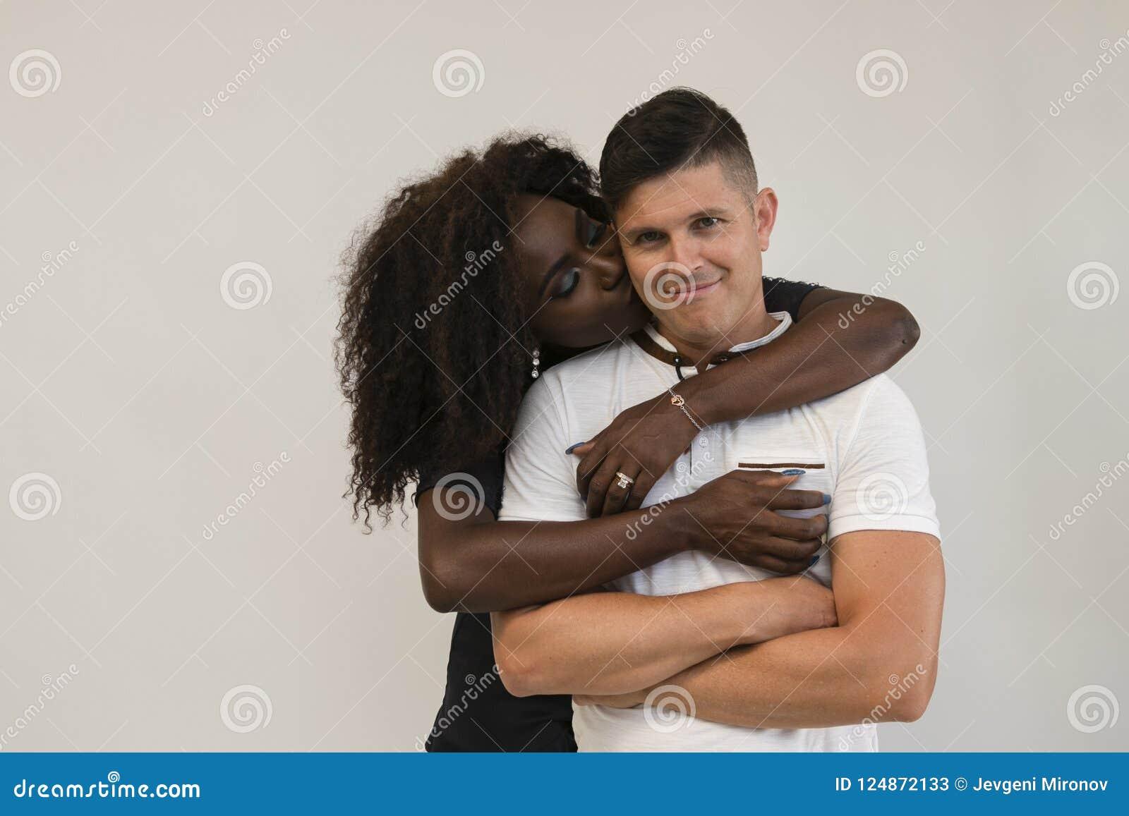 Familia de la raza mixta Esposa blanda joven que abraza a su marido loving