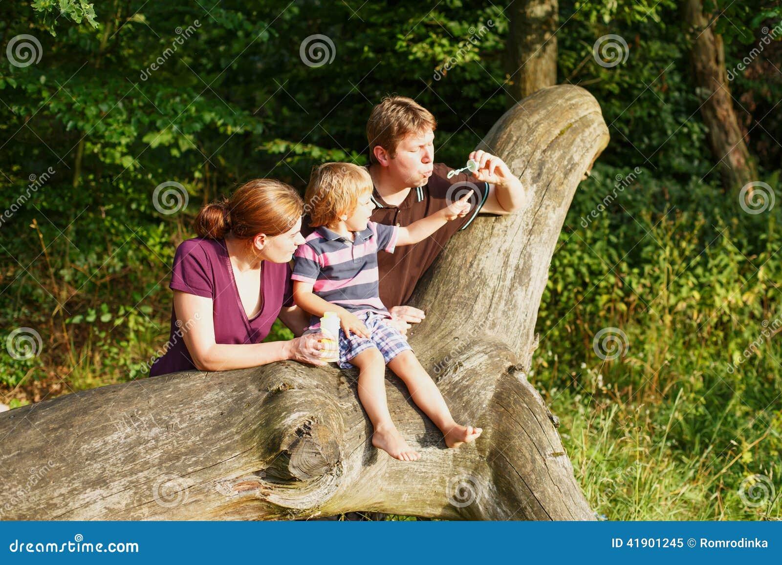 Familia de tres burbujas de jabón que soplan junto en bosque del verano