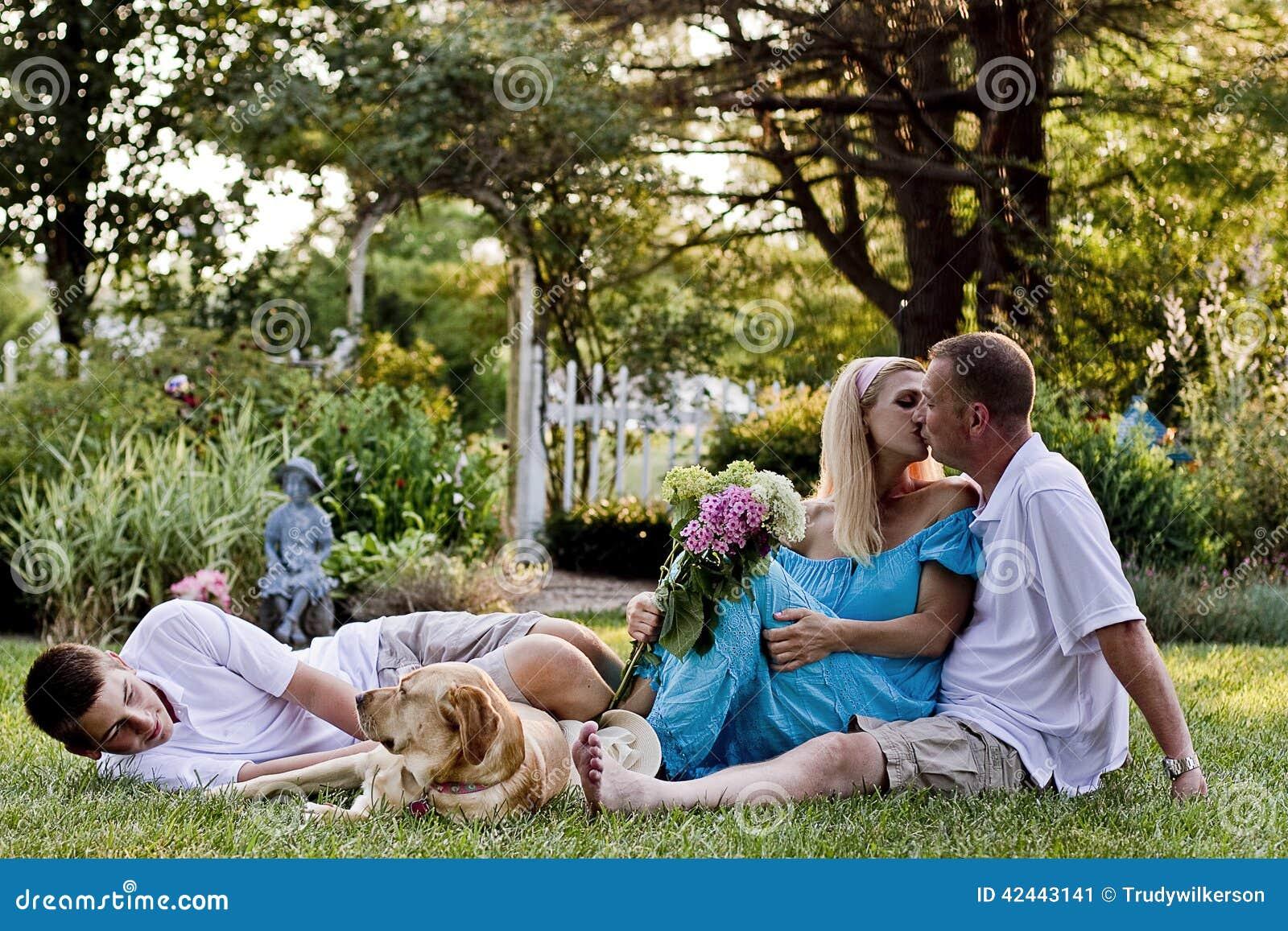Familia de tres delante de jardín de flores