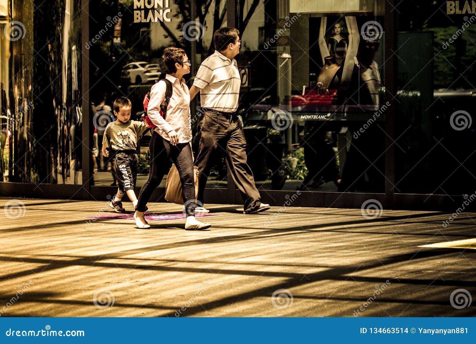 Familia de tres paseos a través de la tienda al por menor de Mont Blanc en compras de gama alta