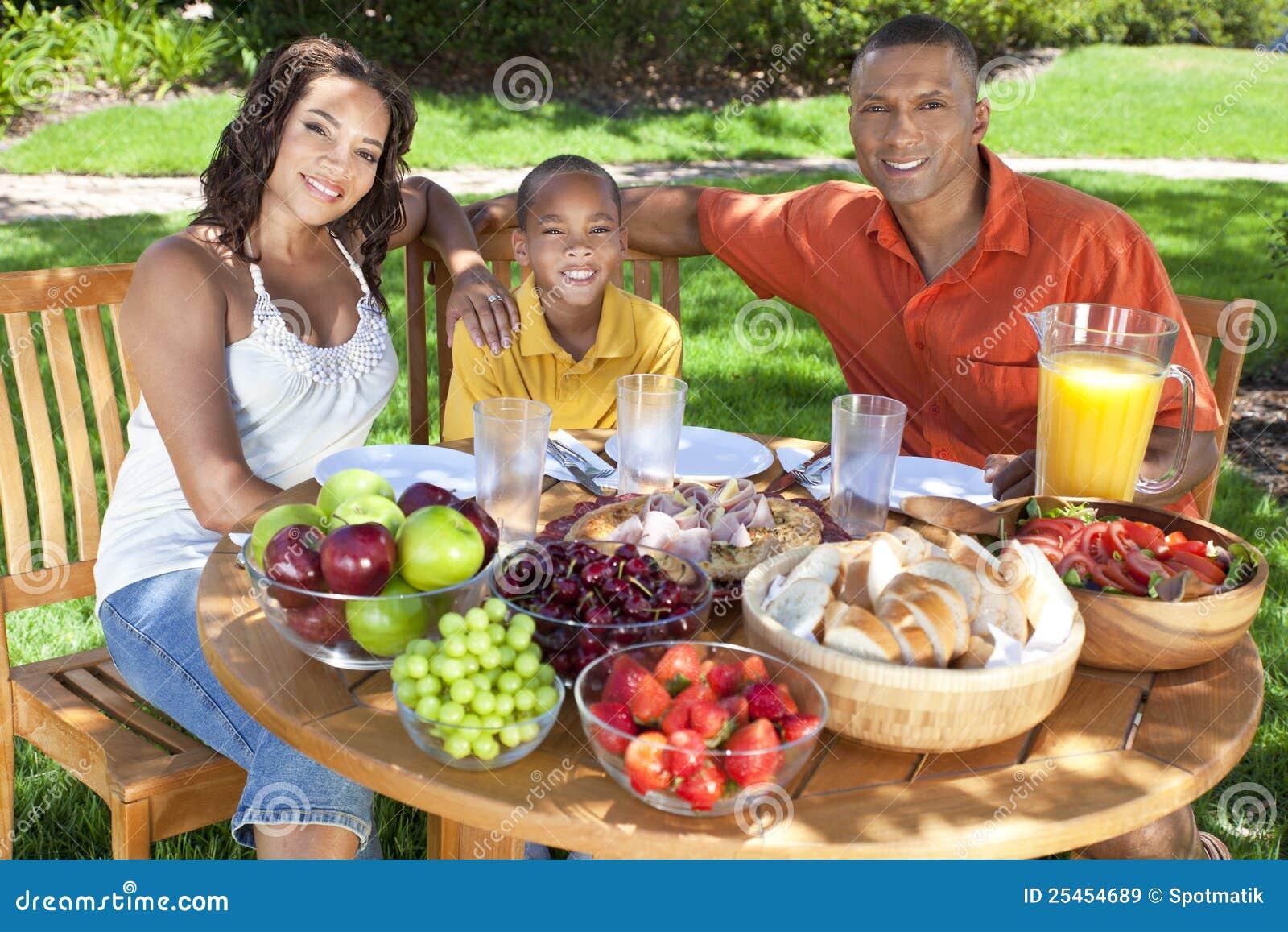 Familia del afroamericano que come el alimento afuera