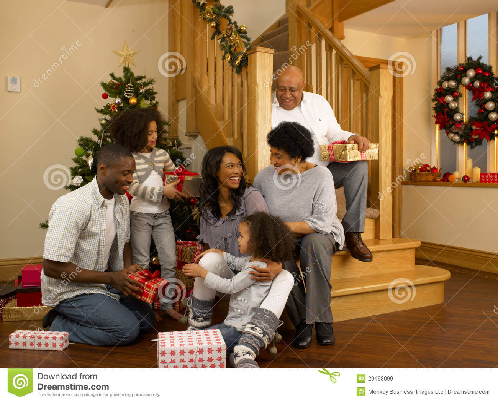 Familia del afroamericano que intercambia los regalos de la Navidad