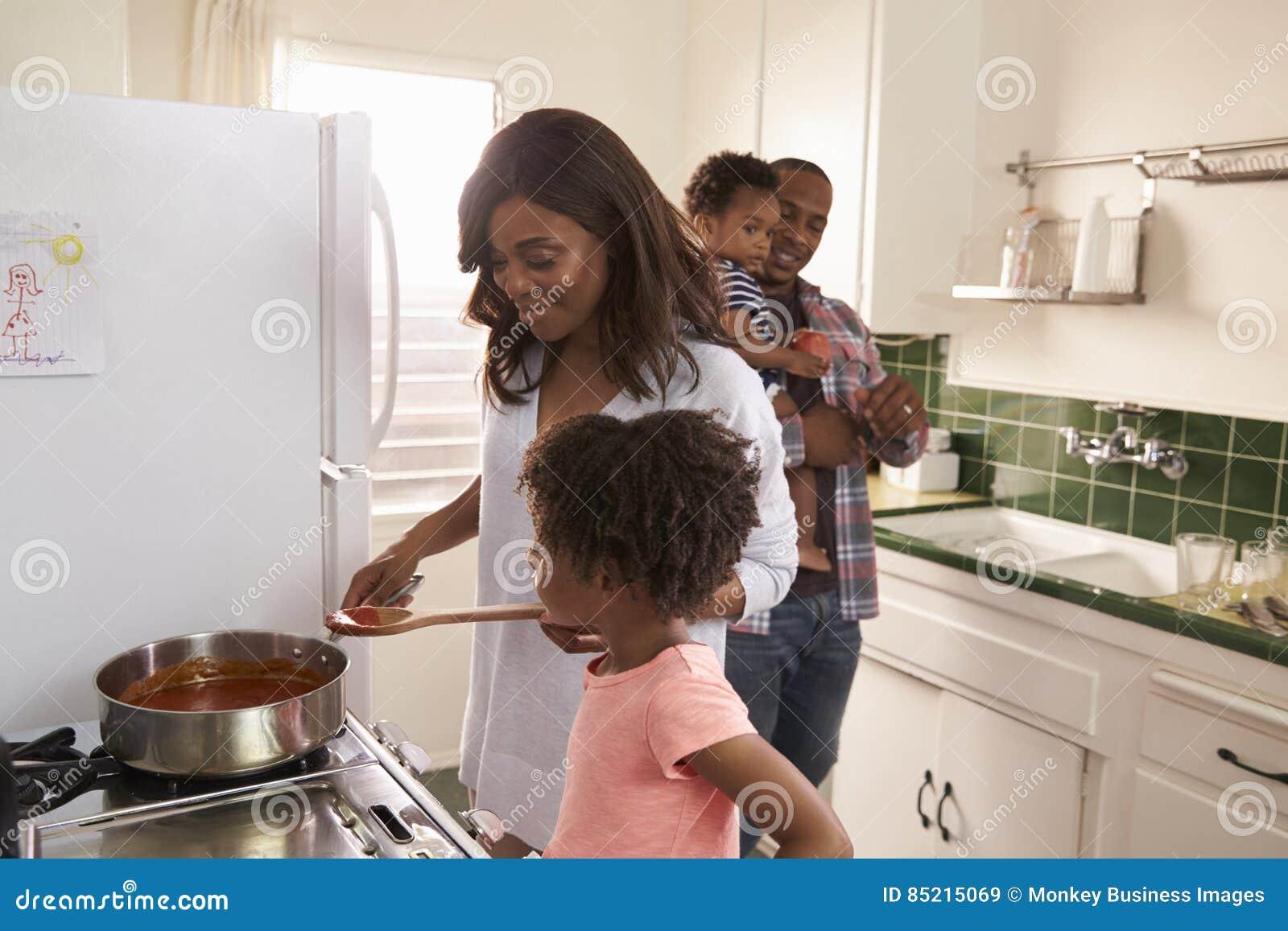 Familia en casa que prepara la comida en cocina junto