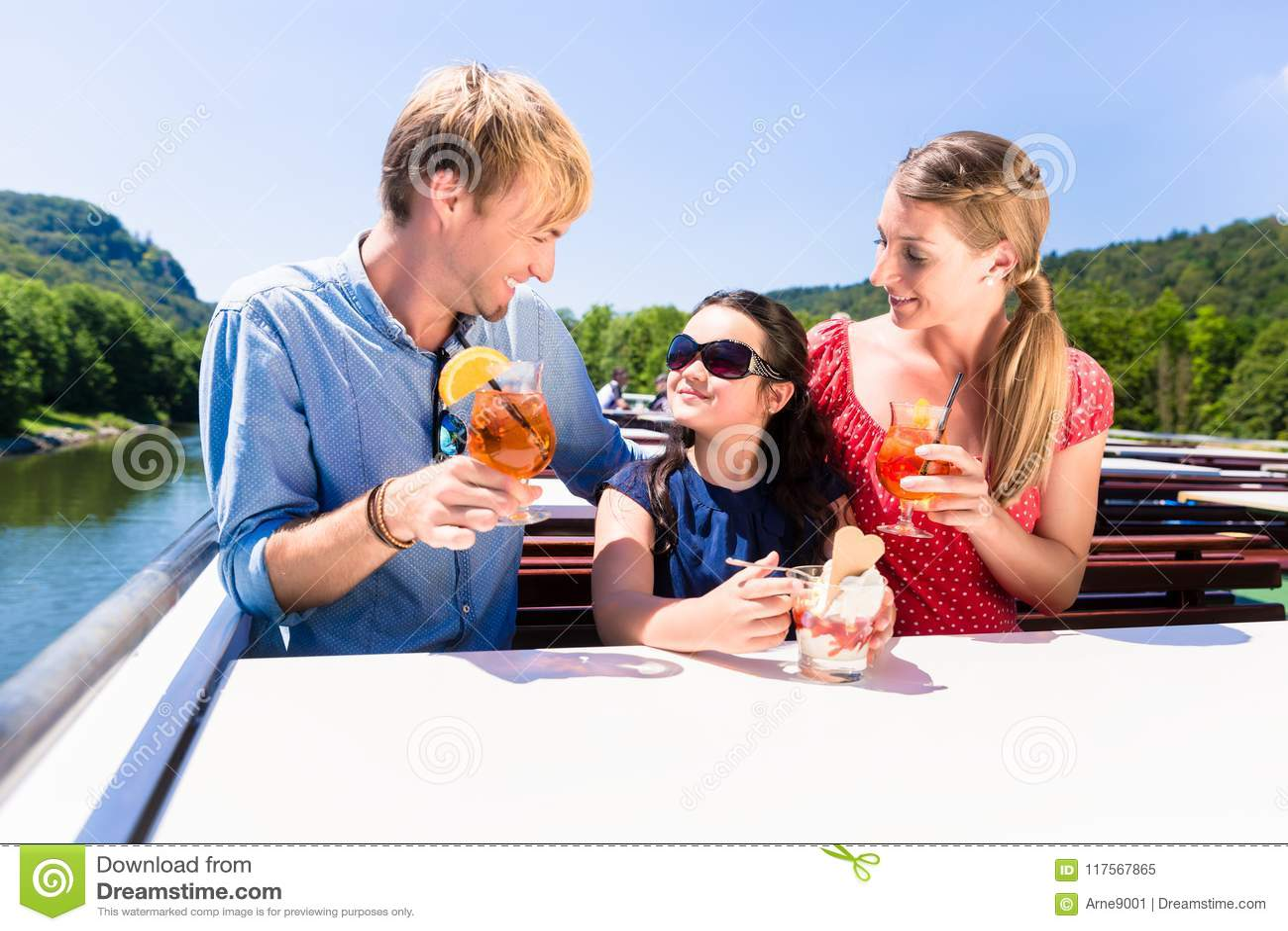 Familia en el almuerzo en travesía del río con los vidrios de cerveza en cubierta
