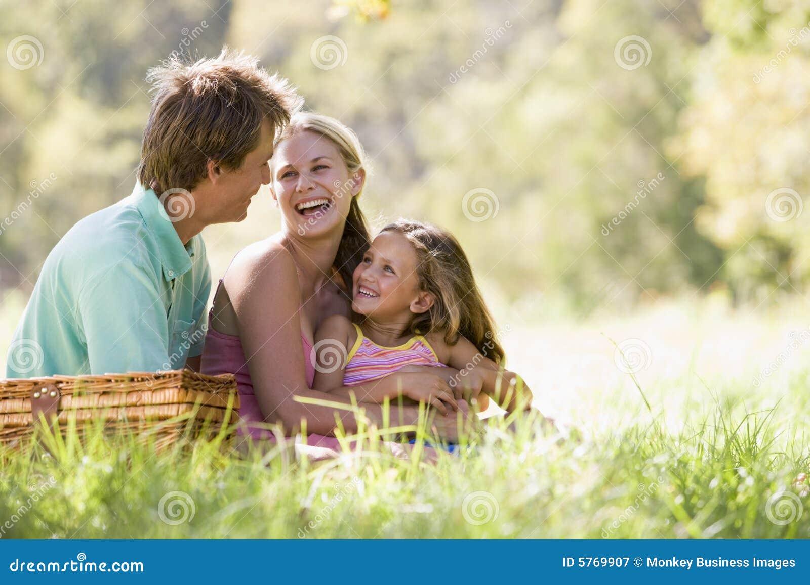 Familia en el parque que tiene una comida campestre y una risa
