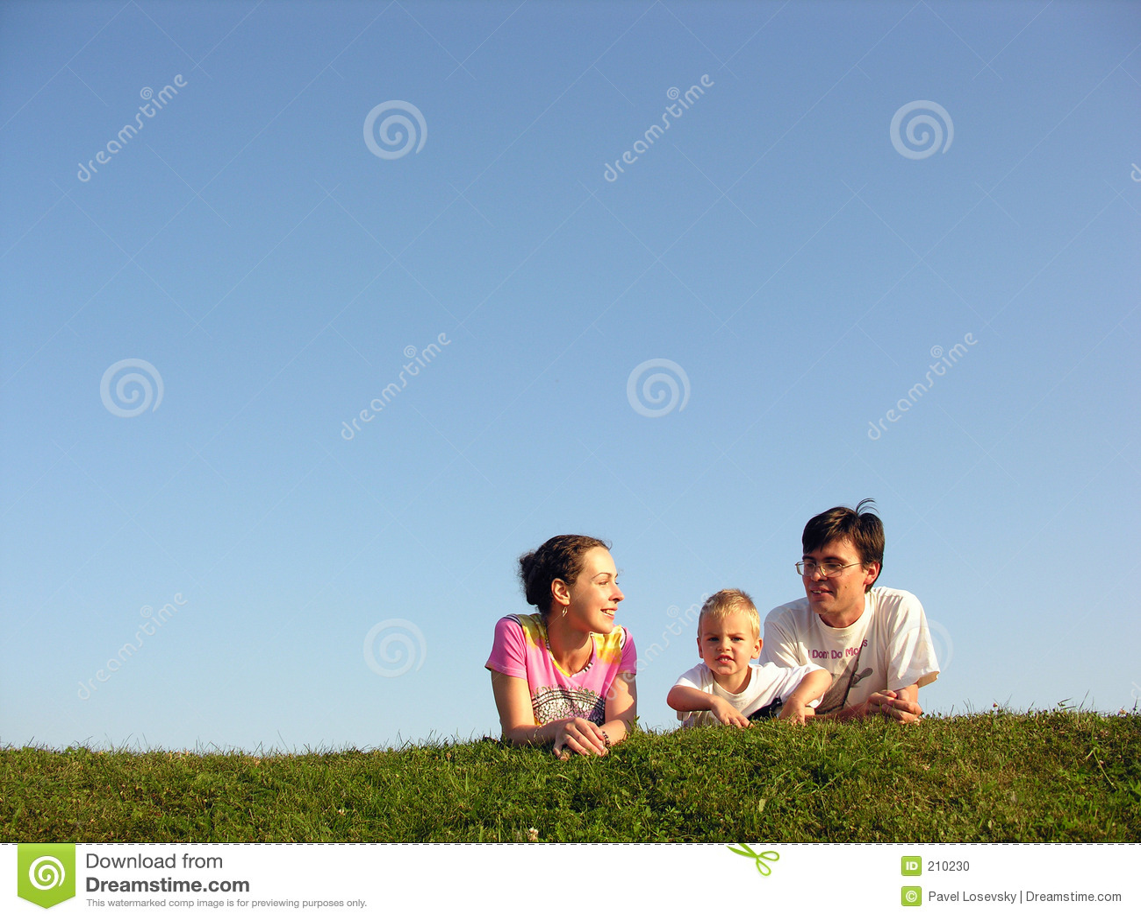 Familia en la hierba bajo el cielo