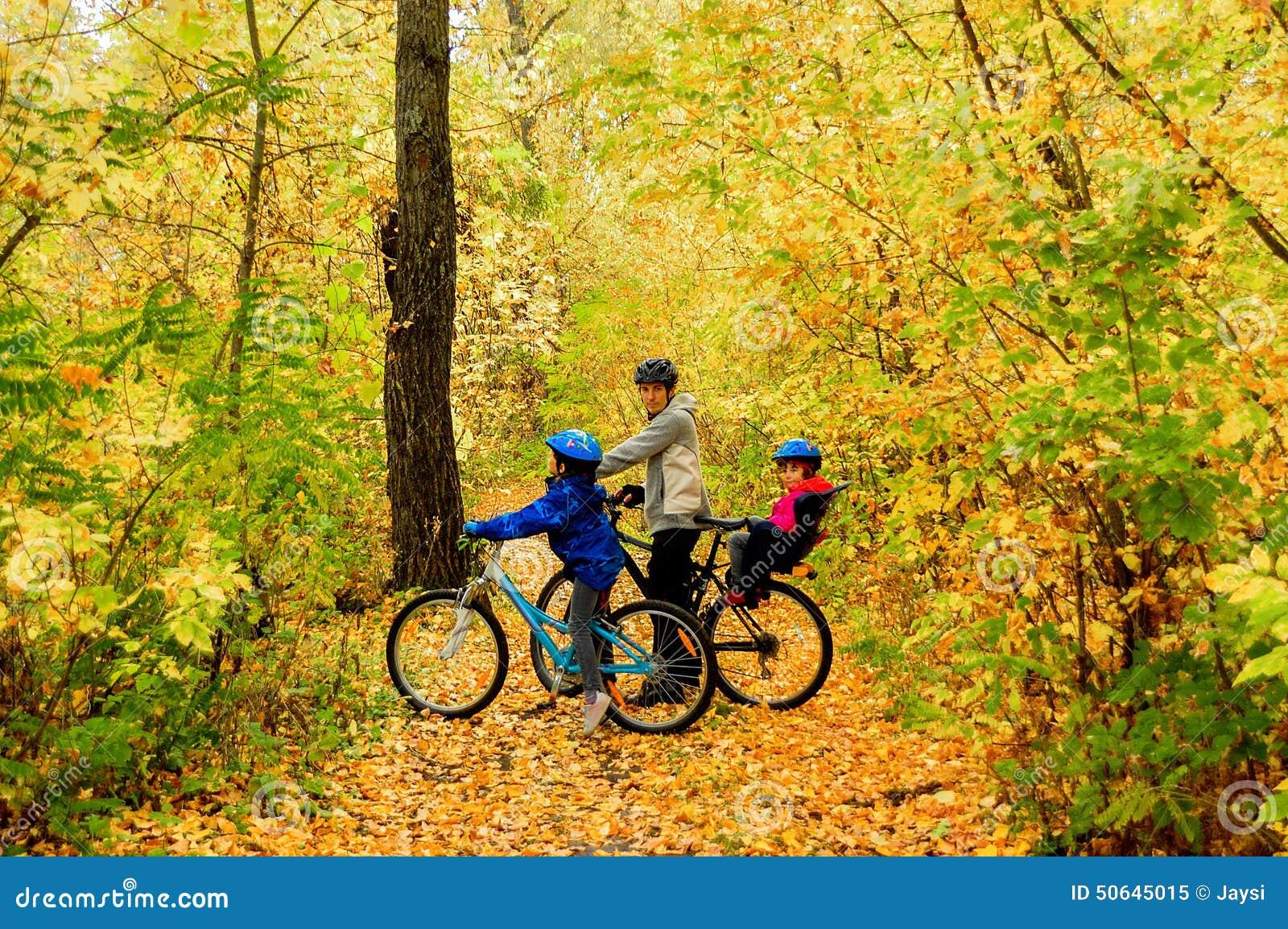 Familia en las bicis en parque del otoño, ciclo del padre y de los niños
