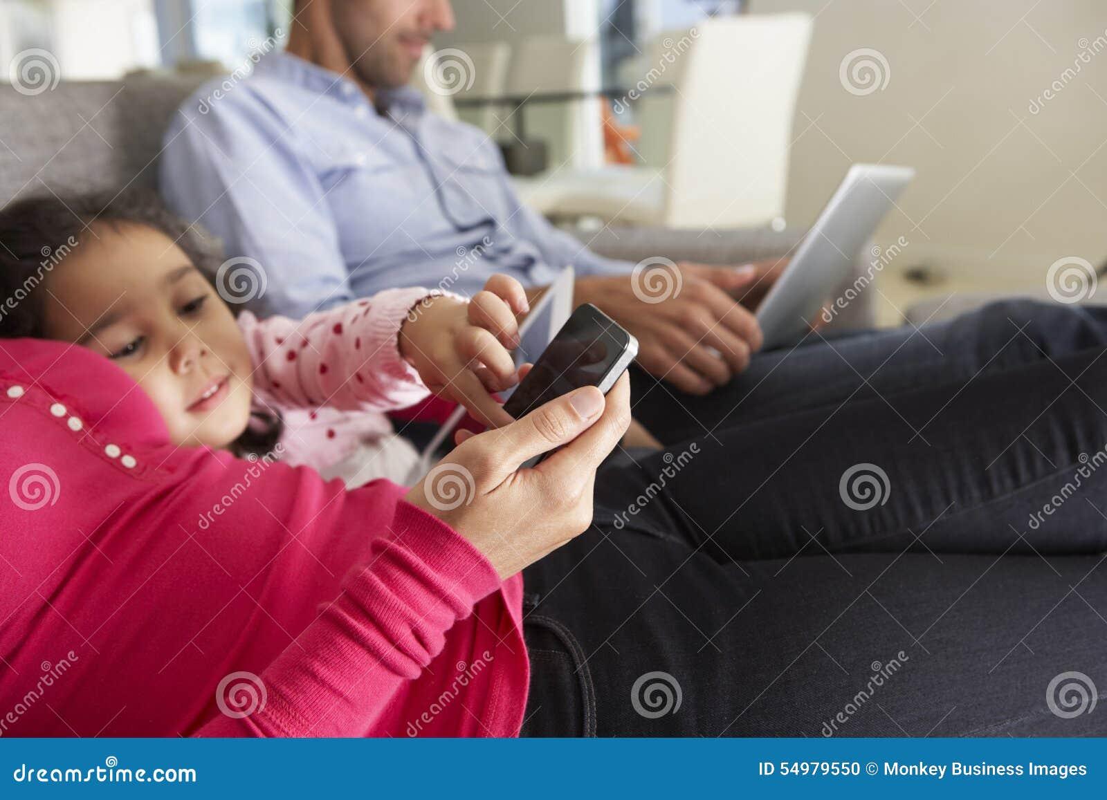 Familia en Sofa With Smartphone, el ordenador portátil y la tableta de Digitaces