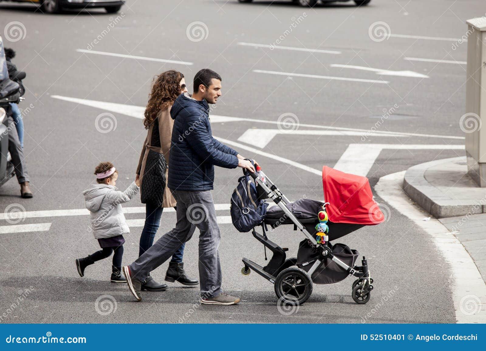 Familia entera con el cochecito que camina en el camino Barcelona, España