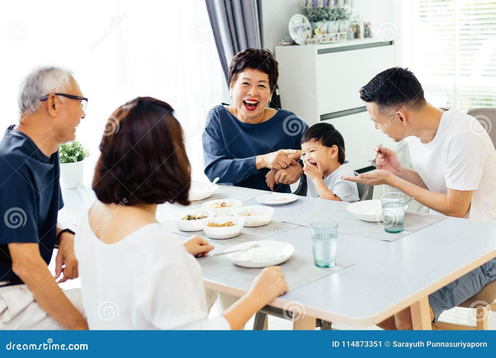 Familia extensa asiática feliz que cena en casa por completo de la risa y de la felicidad