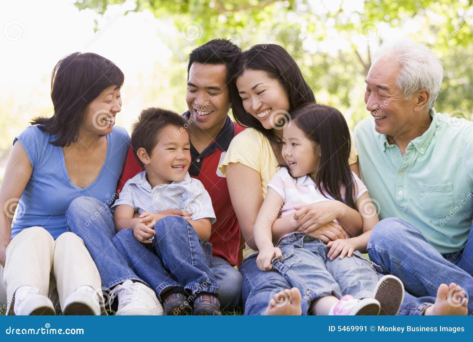 Familia Extensa Que Sienta Al Aire Libre La Sonrisa Imagen