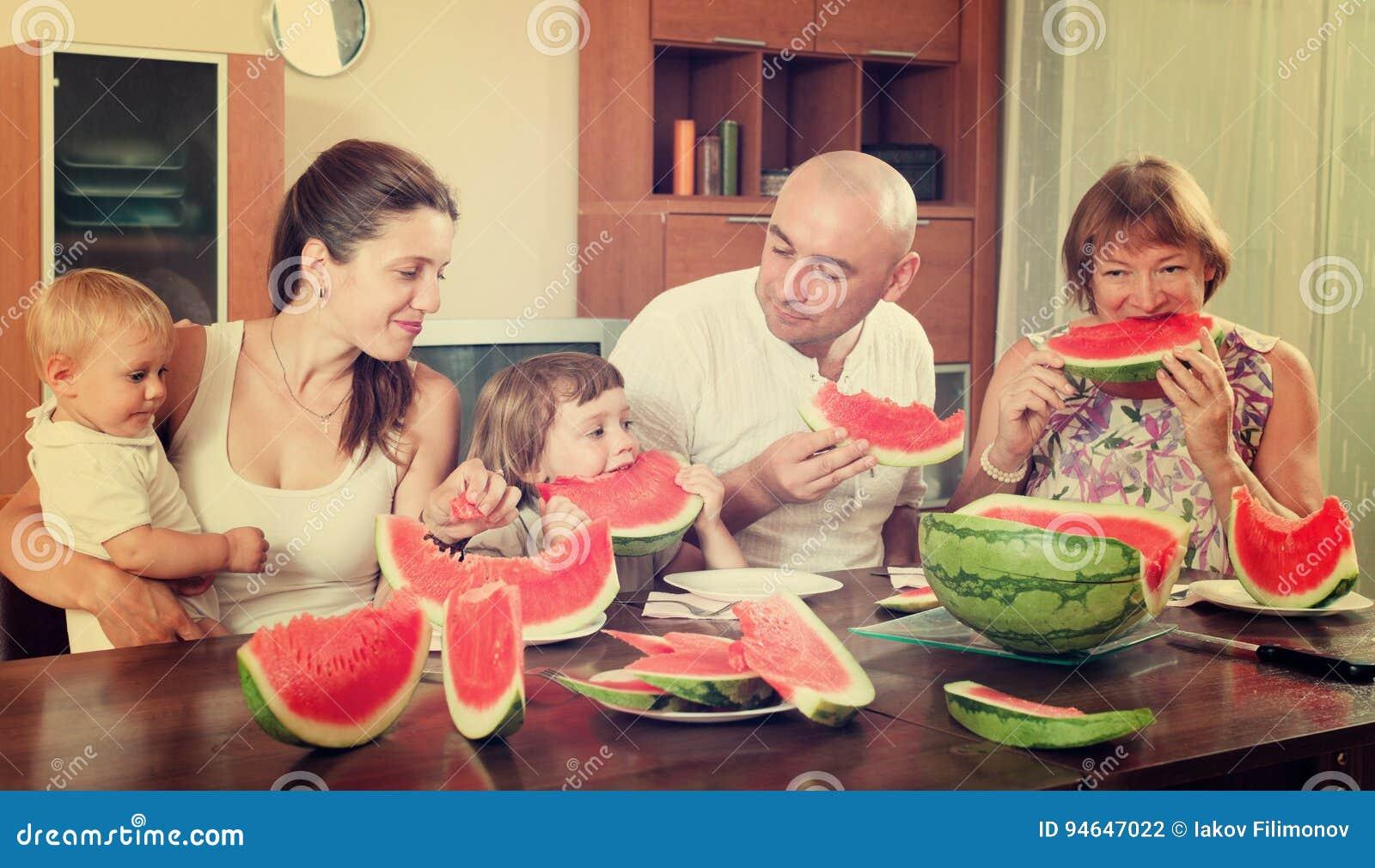 Familia feliz así como la sandía sobre la mesa de comedor