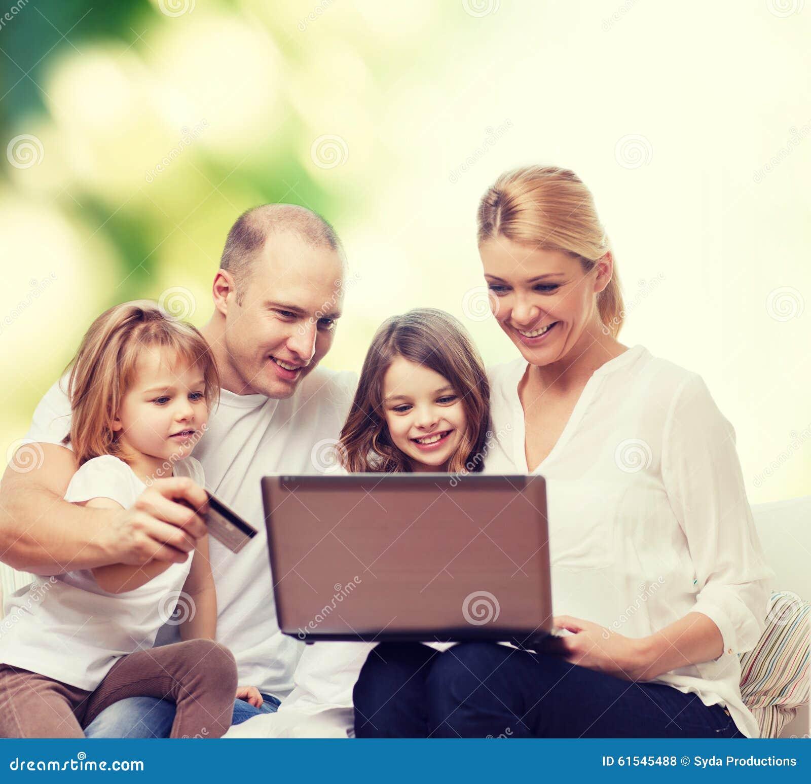 Familia feliz con el ordenador portátil y la tarjeta de crédito
